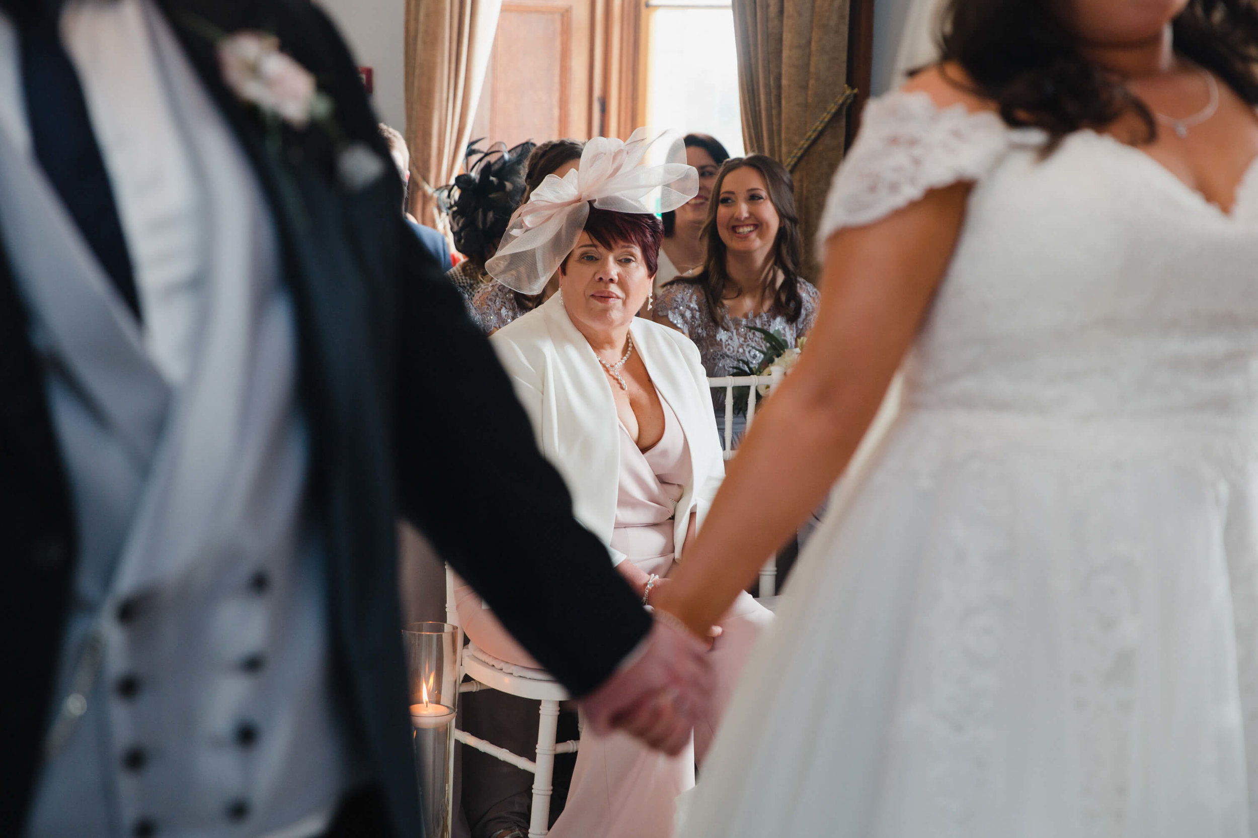 mother of bride watching bride exchange vows at haigh hall