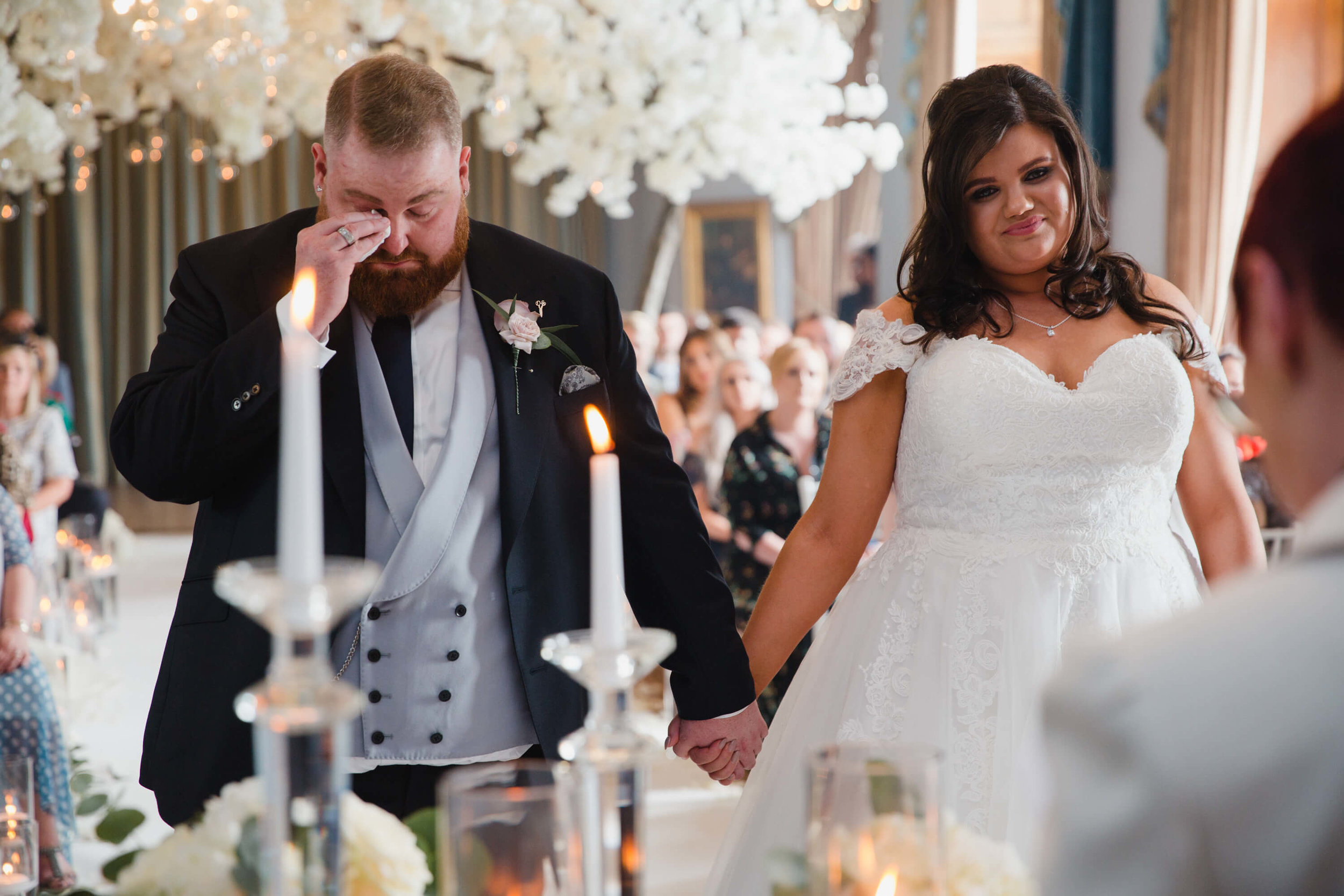 emotional groom wiping away tear into tissue during vows at haigh hall