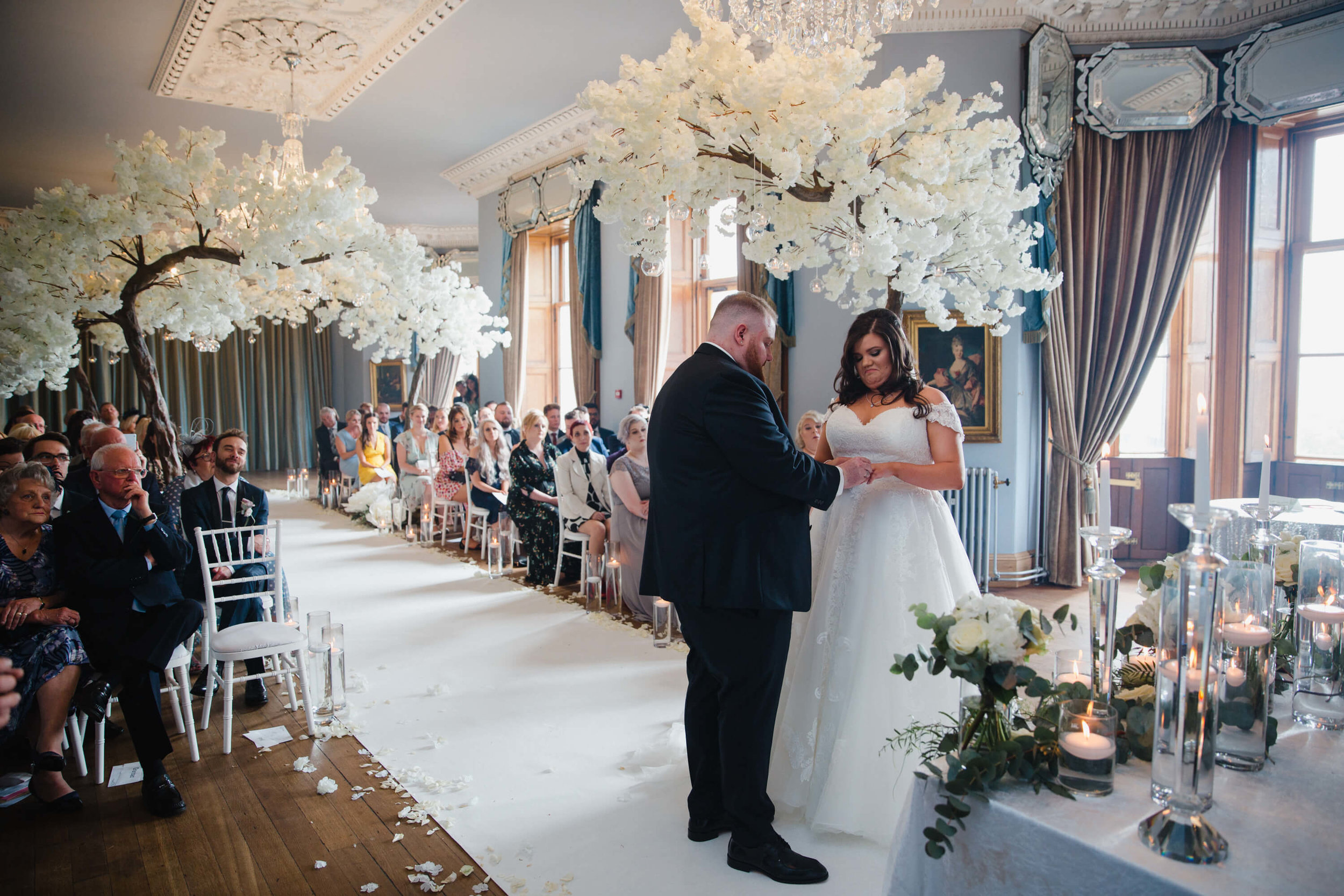 wide angle lens photograph of wedding couple exchanging rings