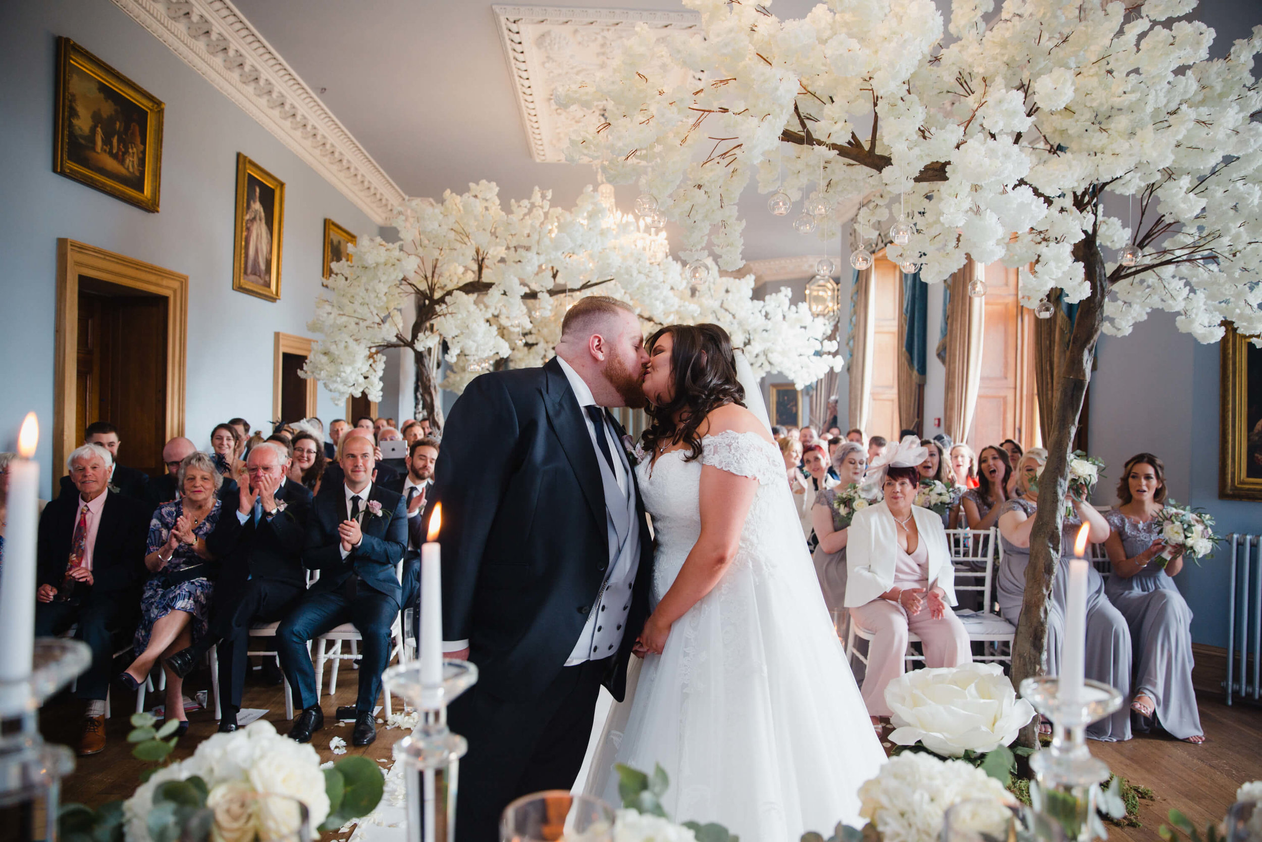 first kiss of bride and groom at haigh hall wedding venue