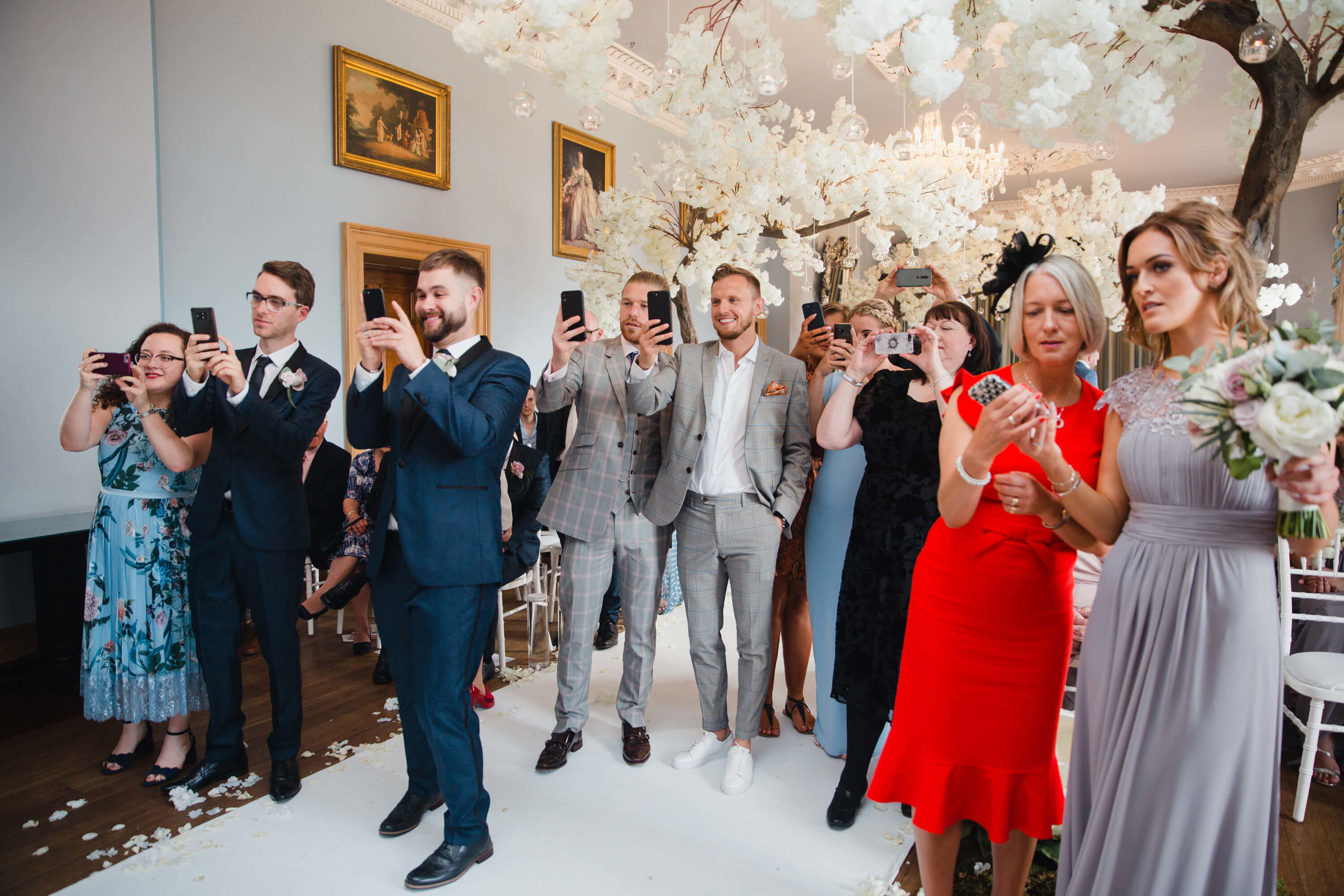 bridal party take photographs of newly wedded couple