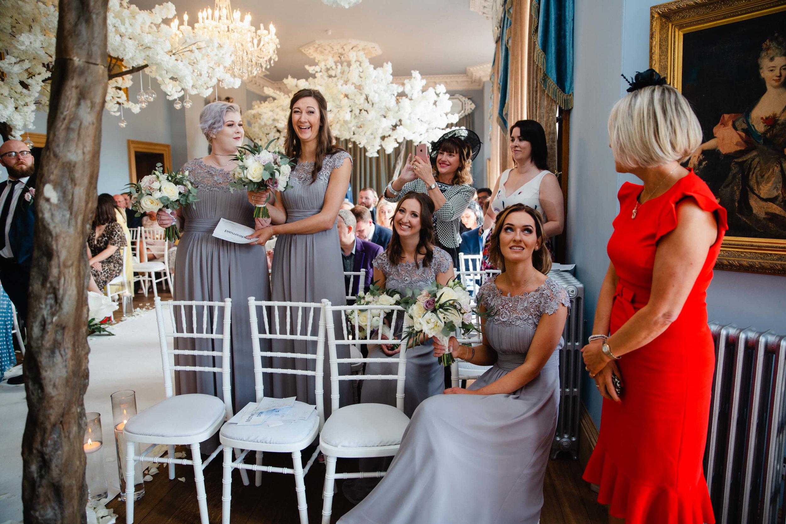 bridesmaids smiling and laughing to camera at haigh hall