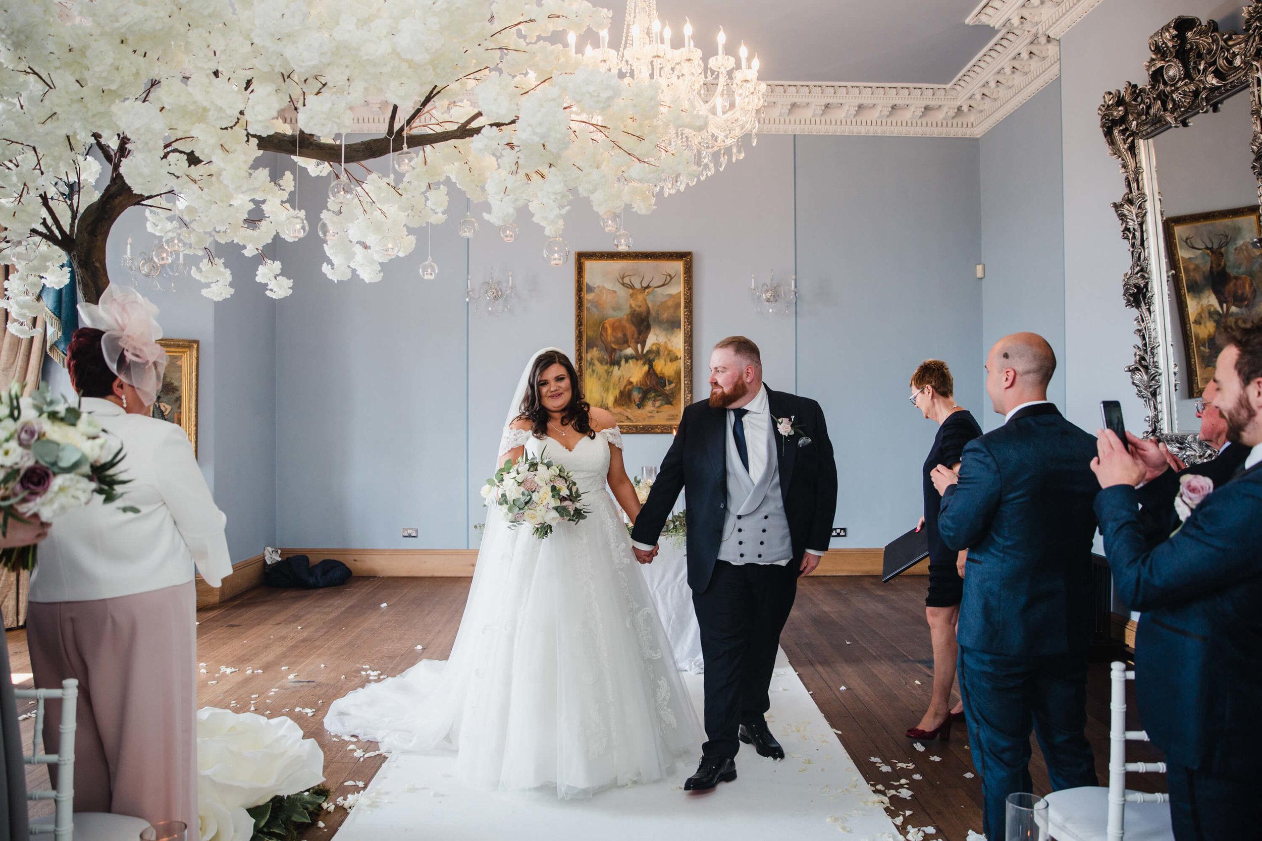 newlyweds walk down aisle as groom looks at bride