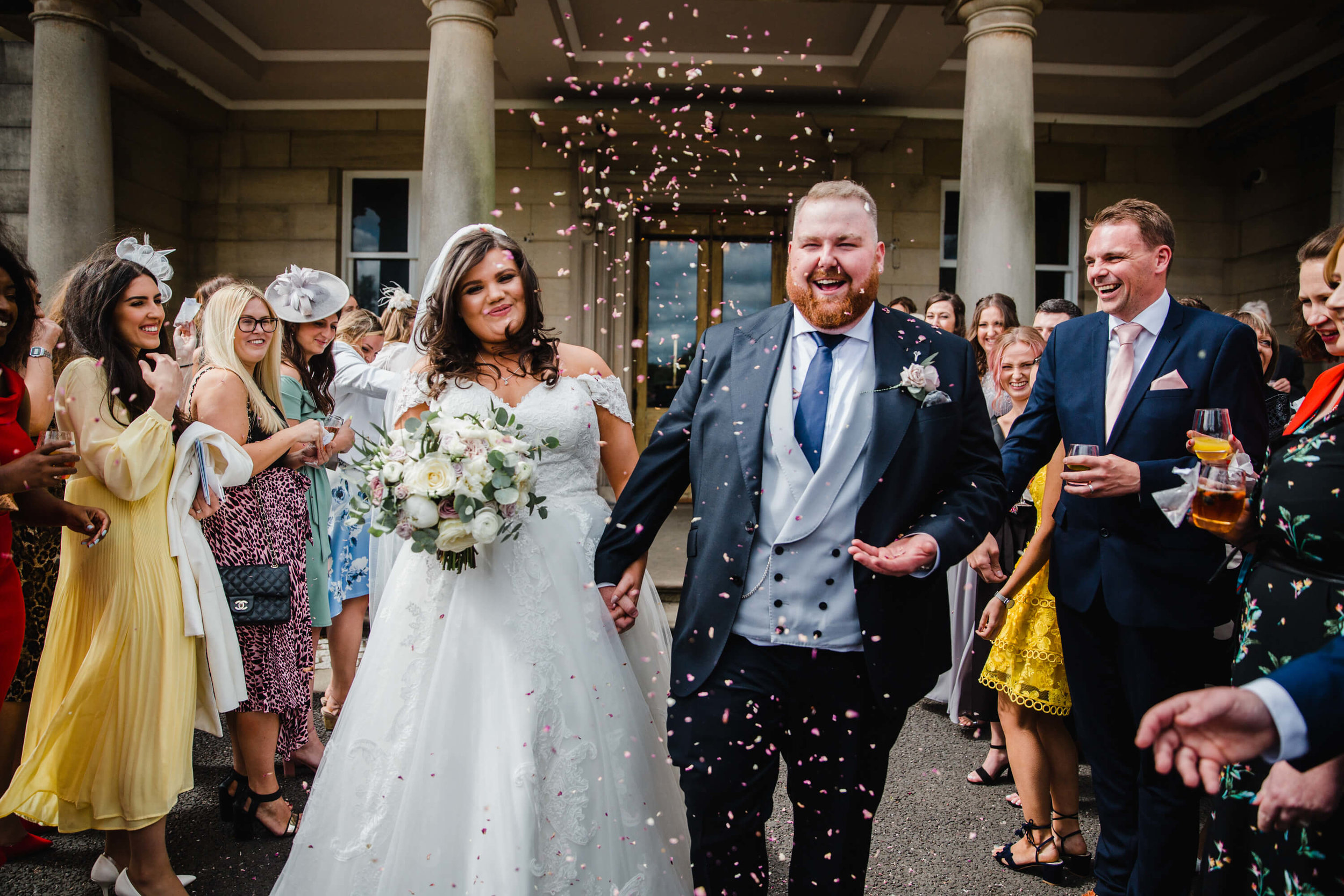 bride and groom run through confetti throwing from wedding party