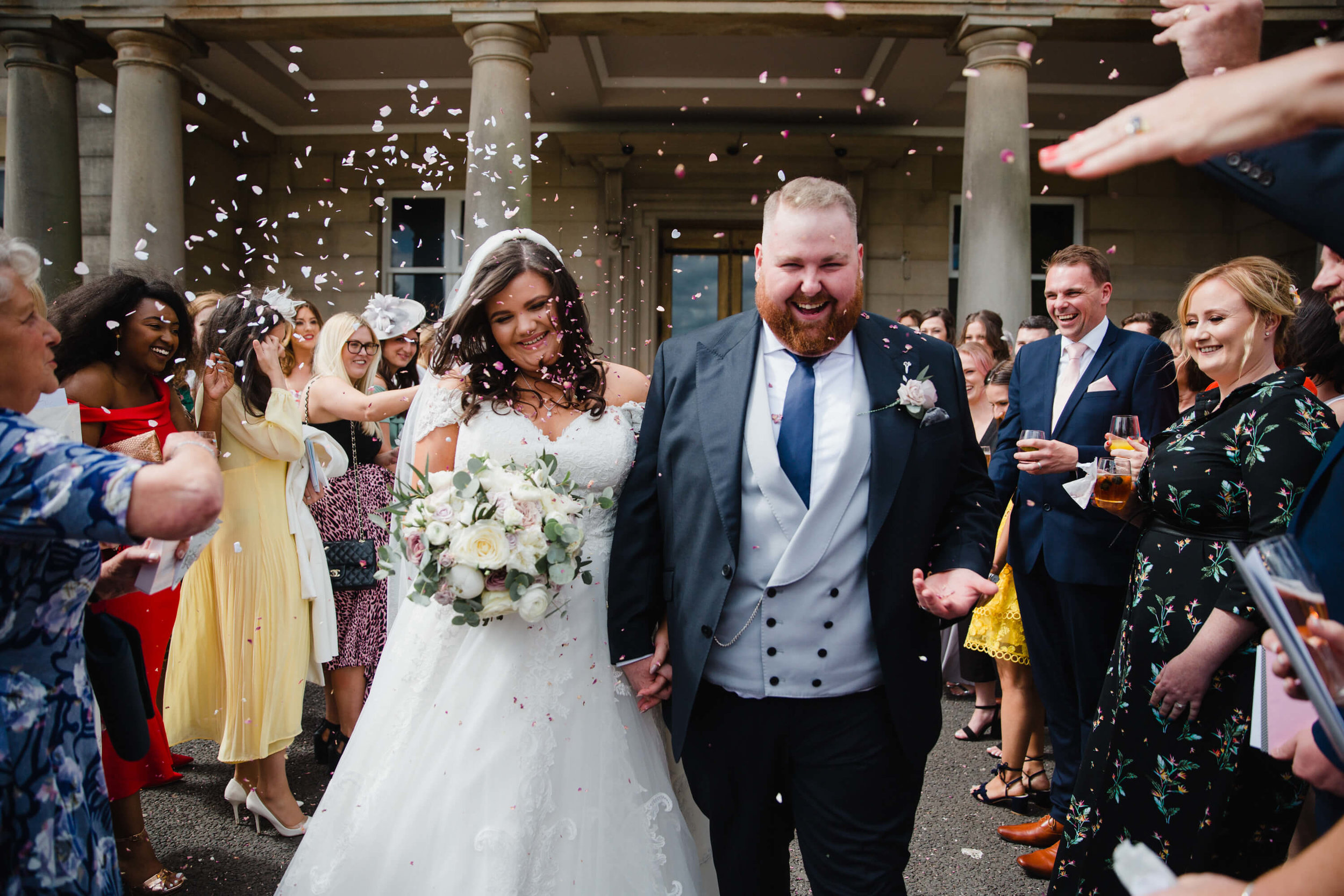 newly wedded couple enjoying confetti from guests after getting married