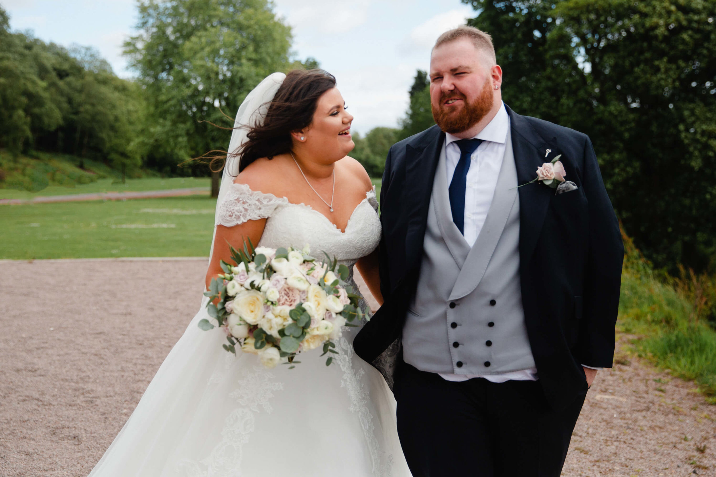 bride and groom stop for portrait in the gardens of haigh hall