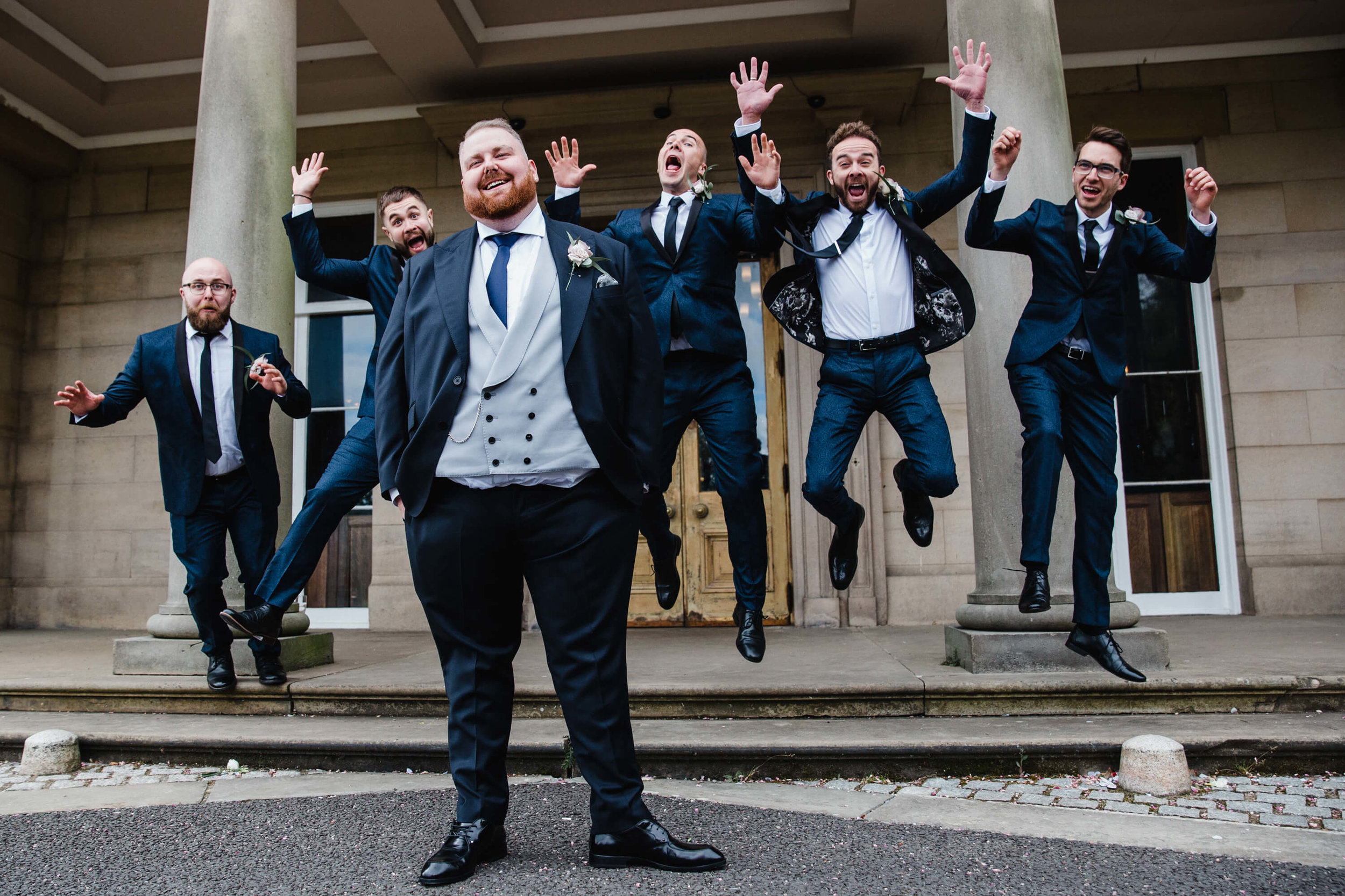 groom and groomsmen pose for jumping portrait in front of haigh hall steps