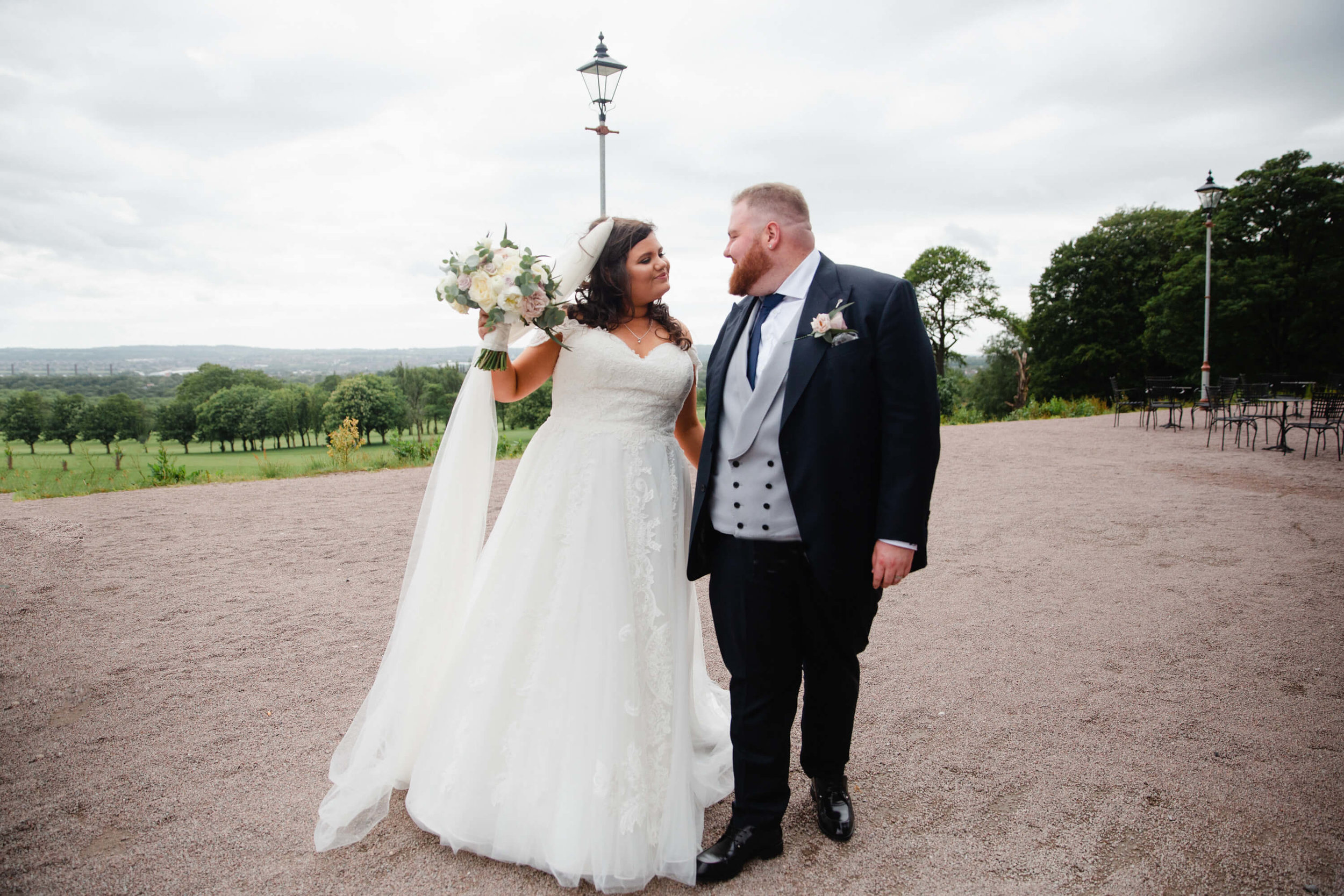 newlyweds holding bouquet of flowers in grounds of haigh hall