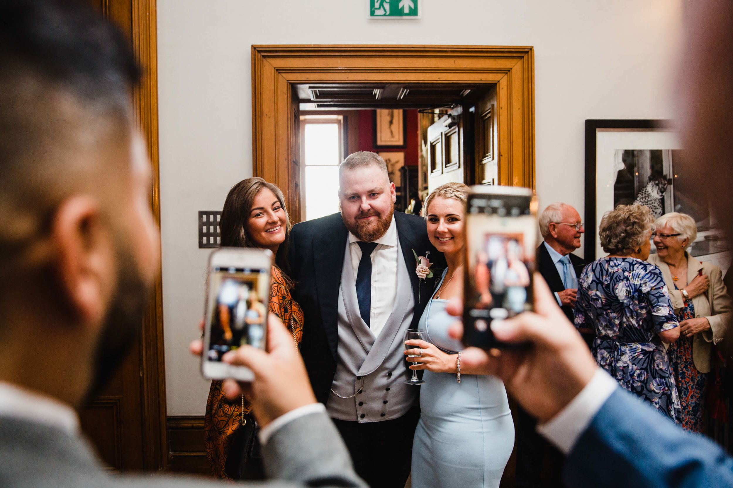 groom with wedding guests pose for camera phones during drinks reception