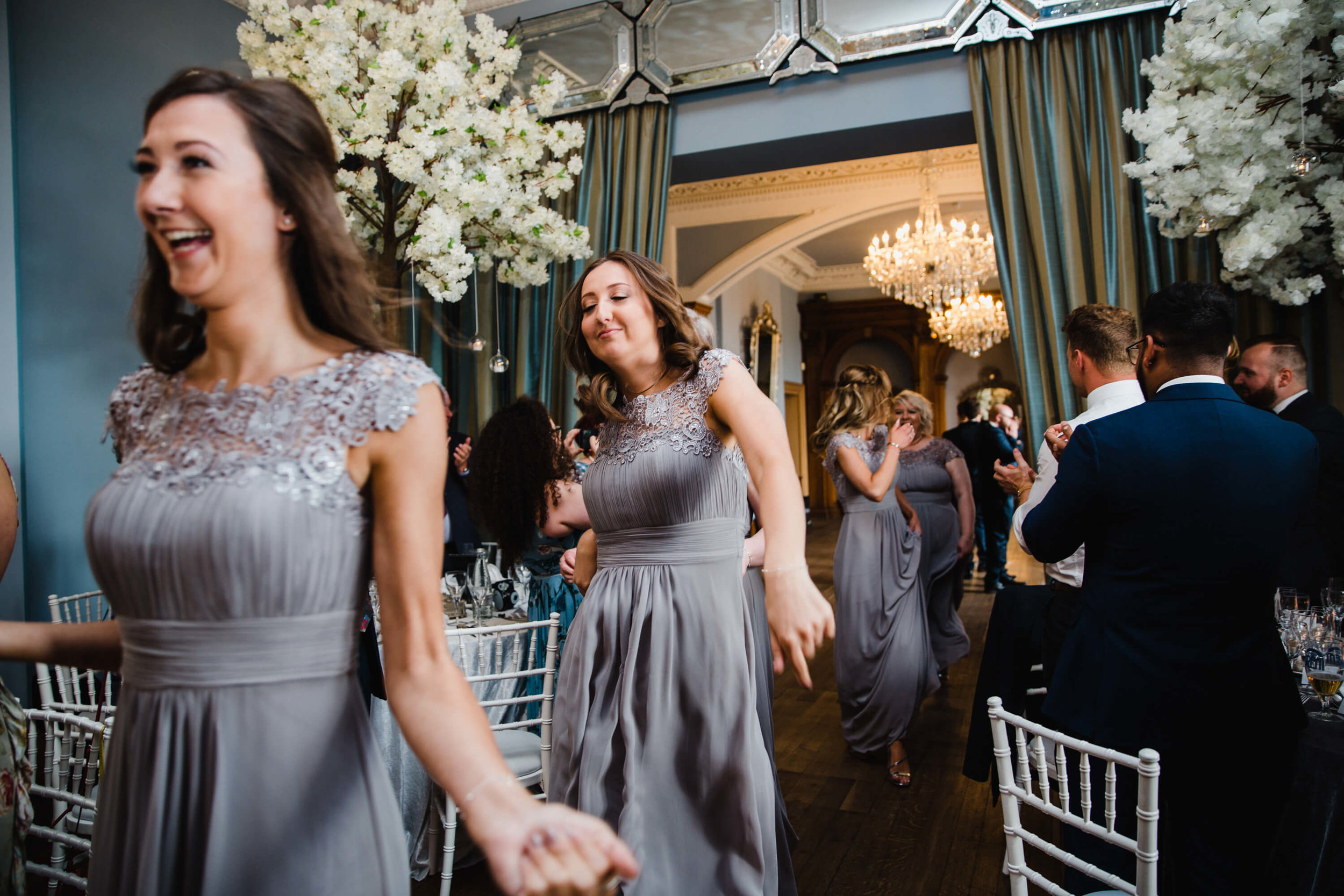 bridesmaids being clapped into wedding breakfast room by guests