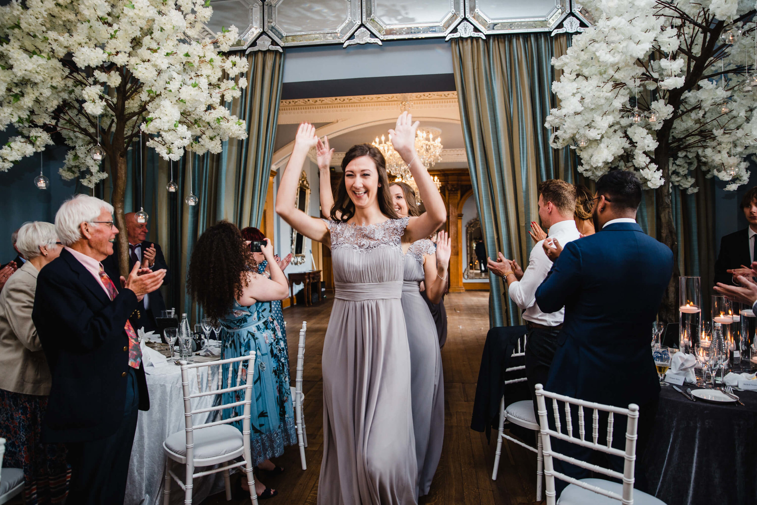 bridesmaids entering wedding breakfast room greeted by clapping wedding guests
