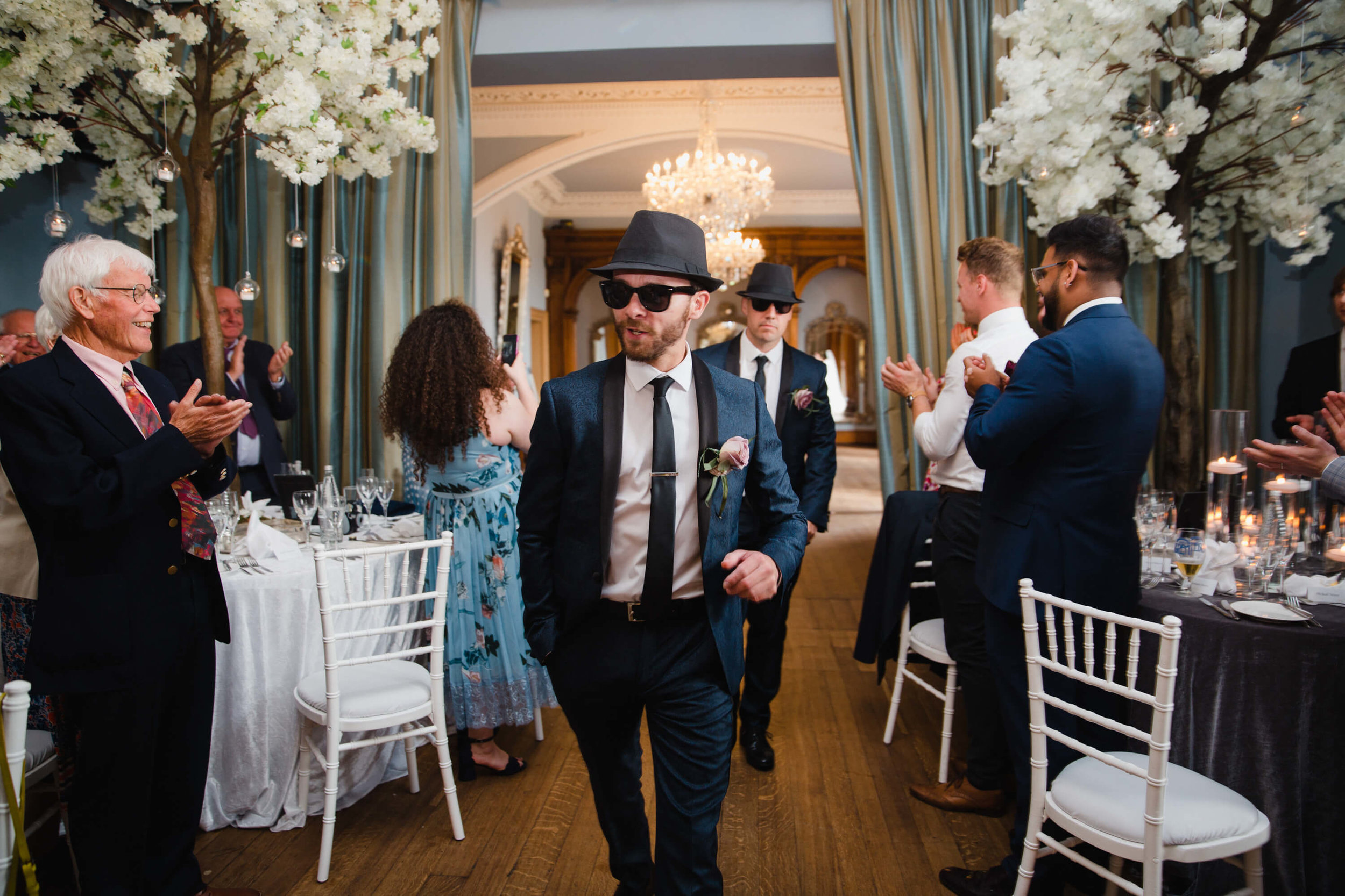 best men wearing hats and sunglasses being clapped into wedding breakfast room