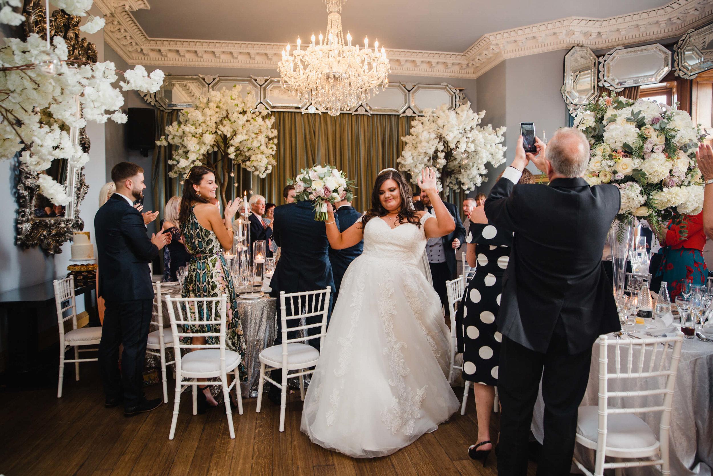 bride being cheered into wedding breakfast room