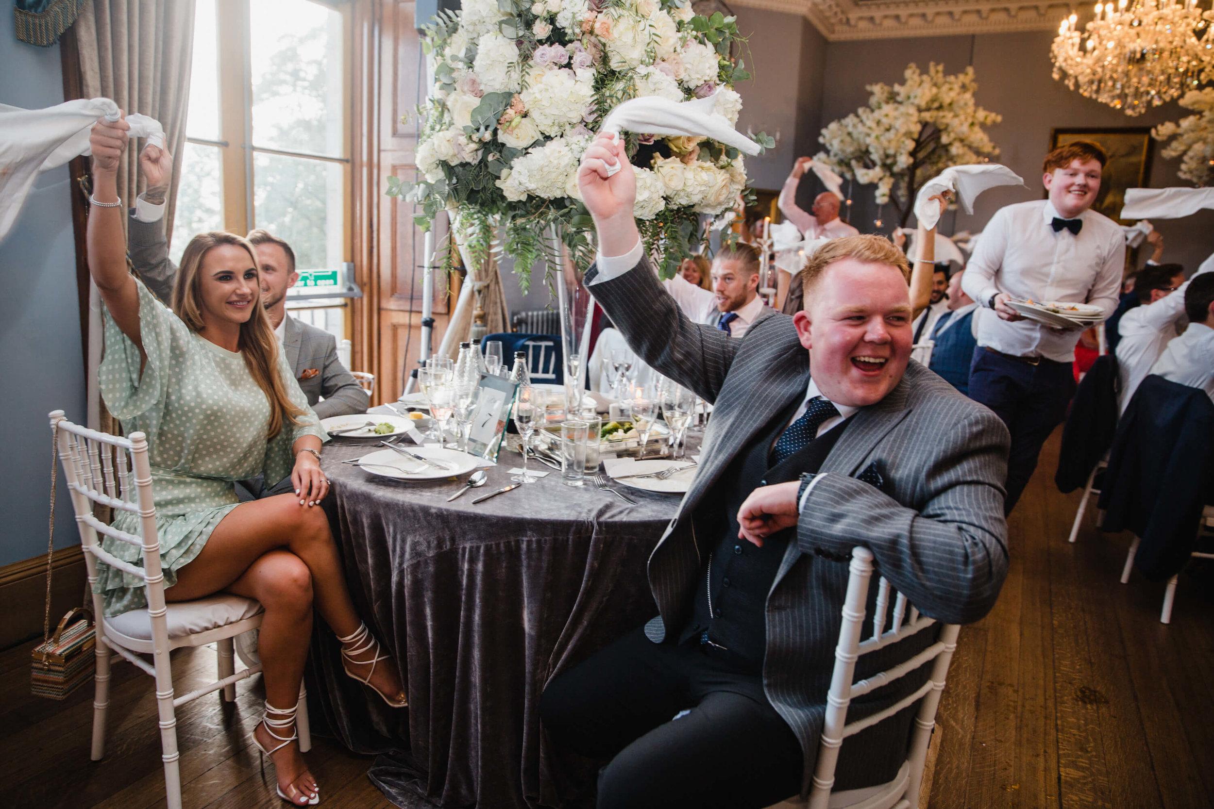 wedding guests waving handkerchiefs while singing