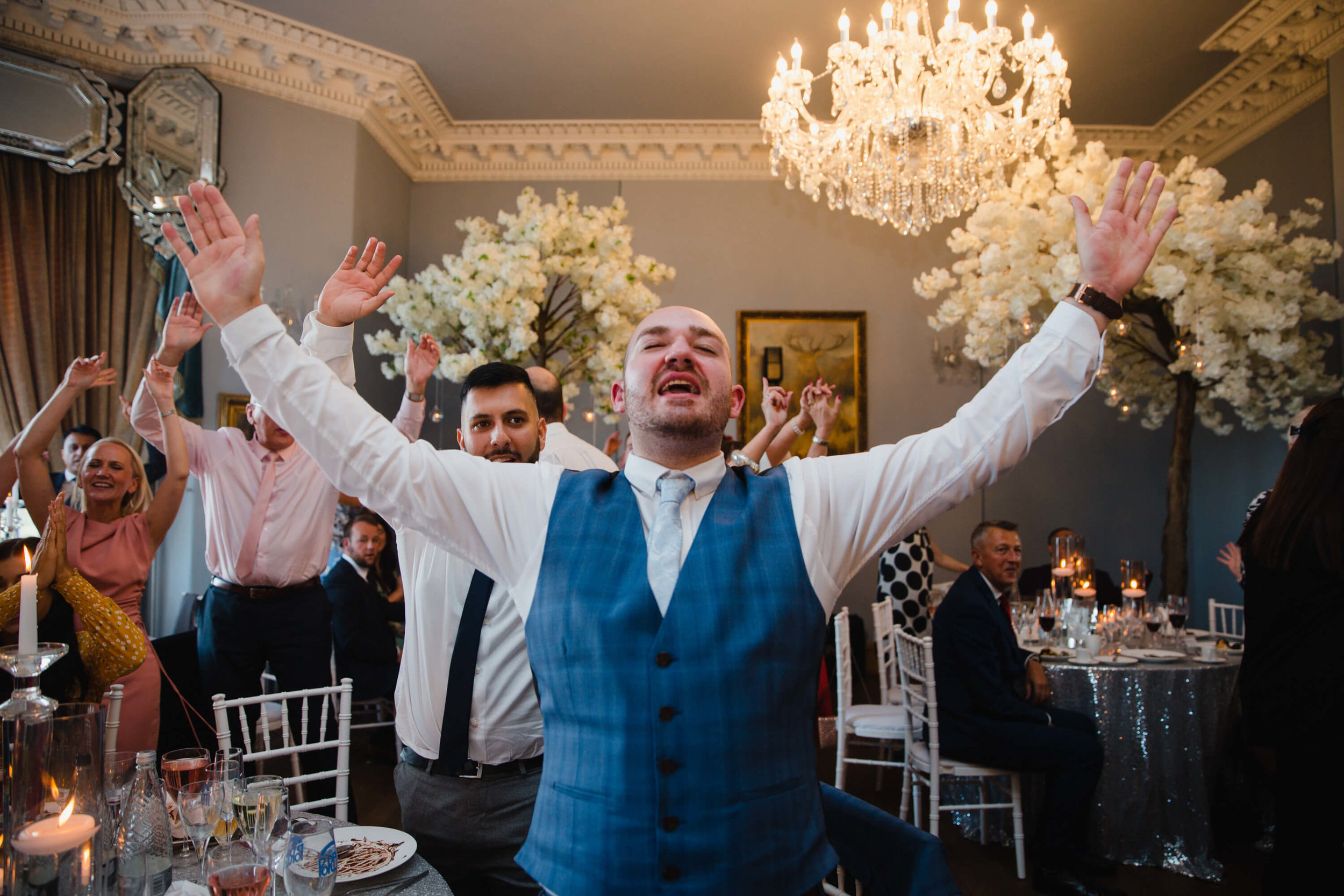best man waving hands in air while singing