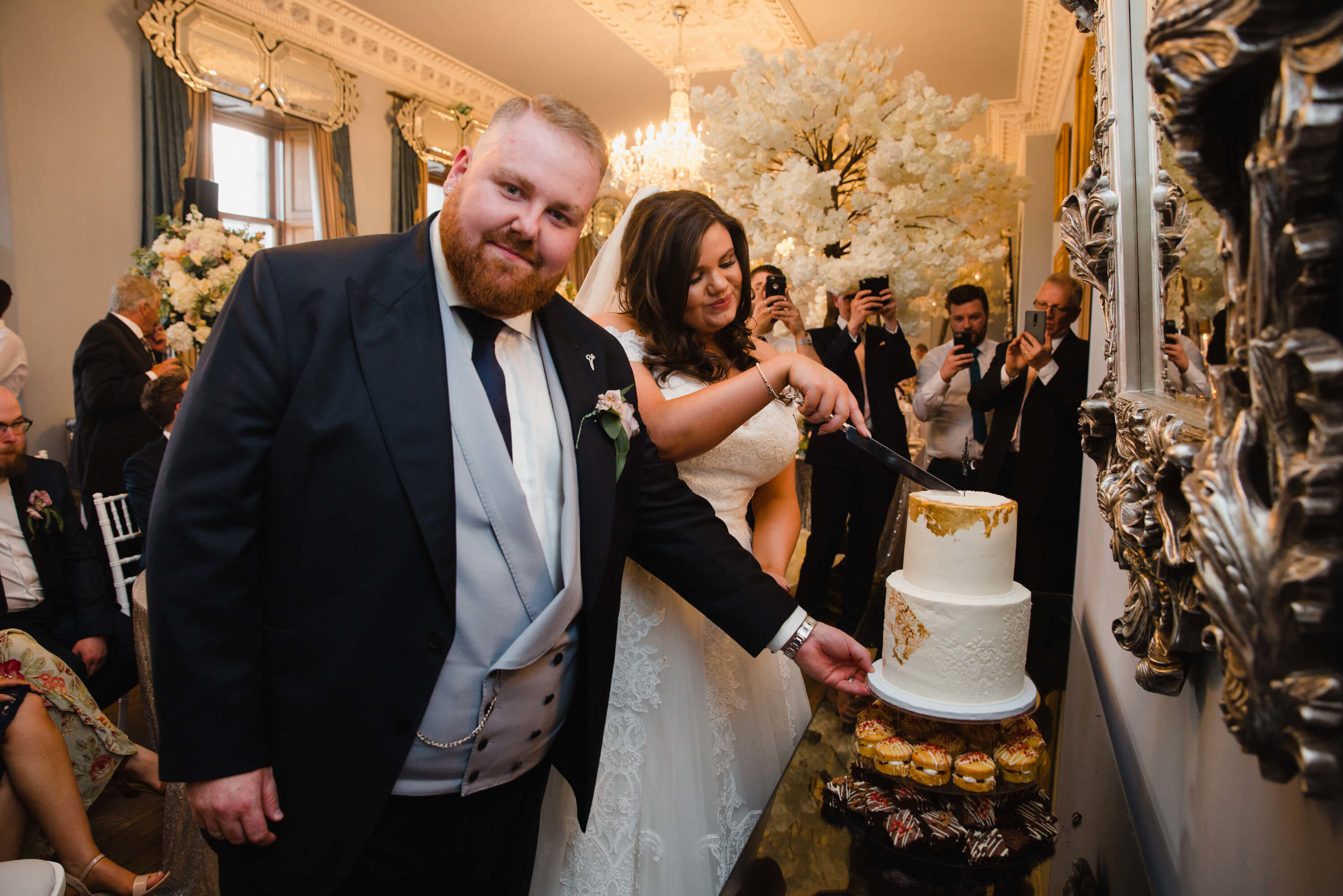 bride and groom cutting wedding cake at haigh hall