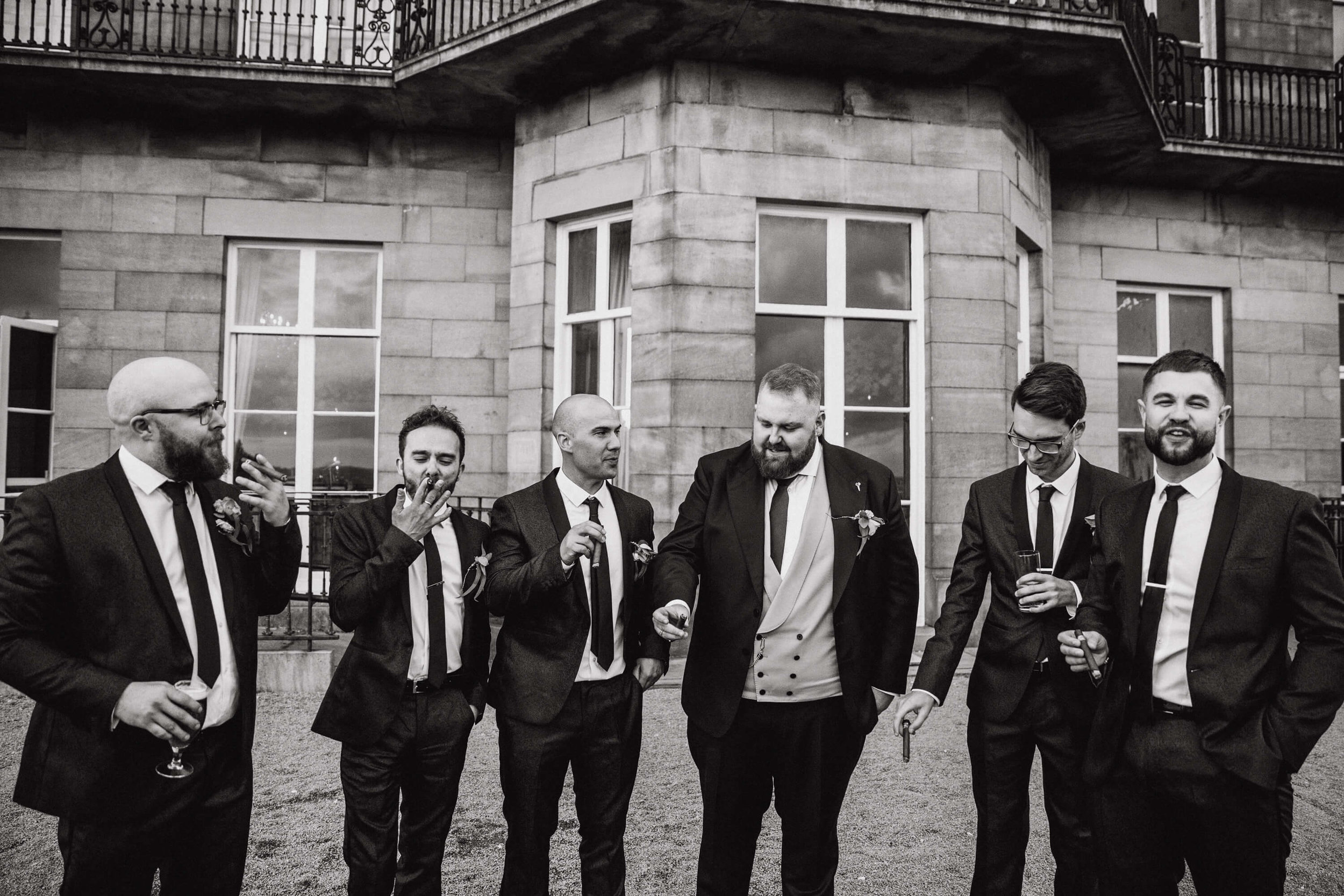 black and white photograph of groomsmen smoking cigars in gardens of haigh hall