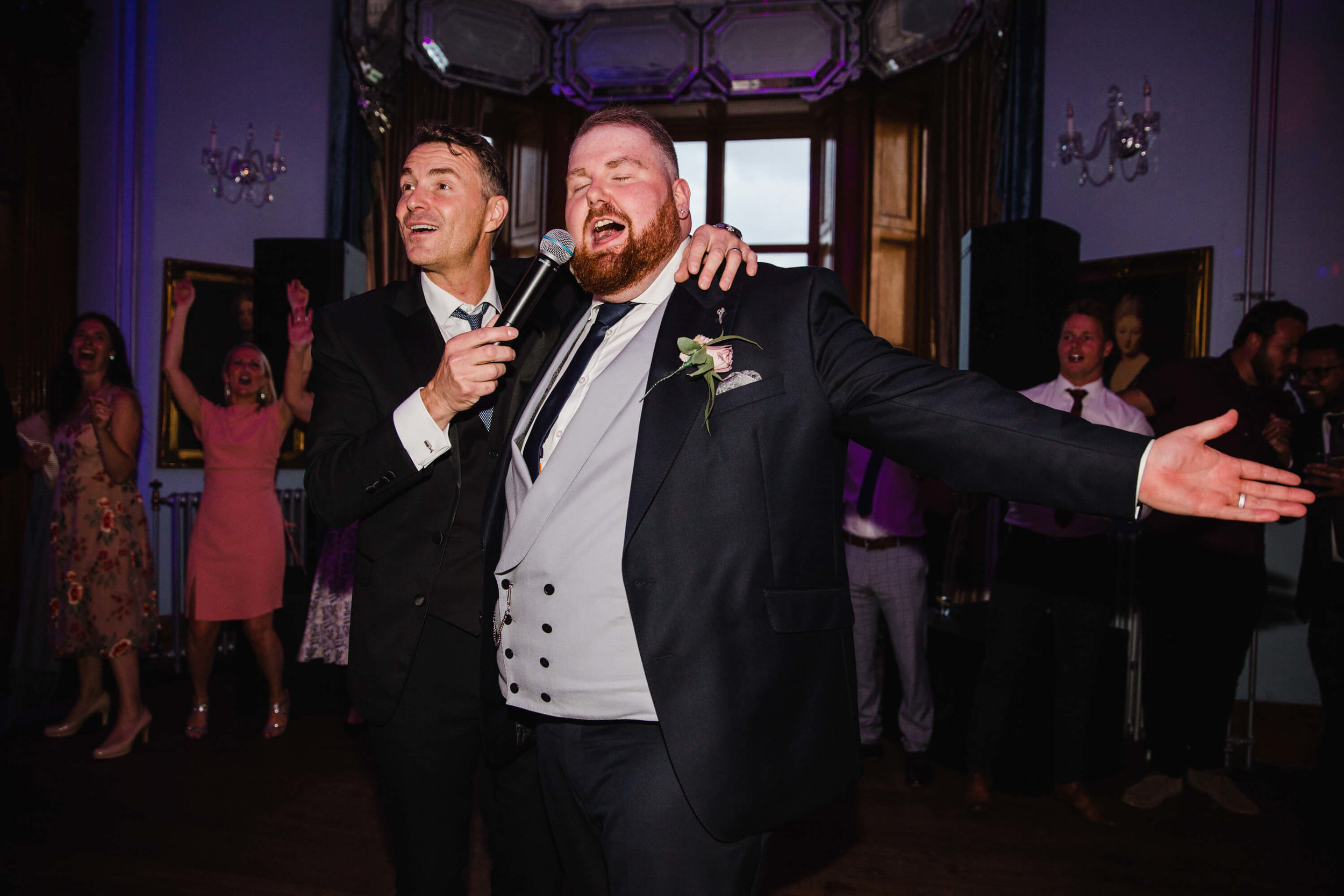 groom singing on dancefloor with howard wing