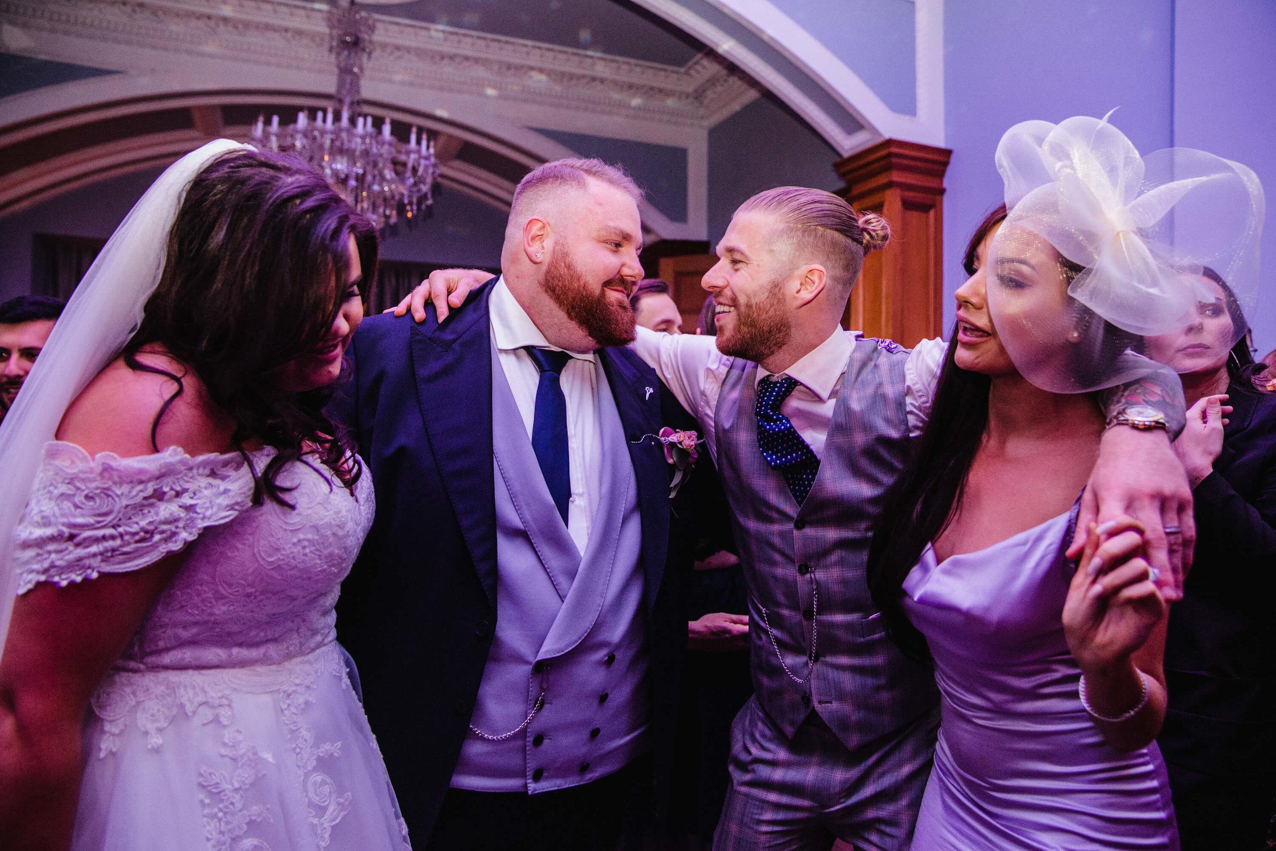 newlyweds exchange hug and congratulations on dancefloor at haigh hall