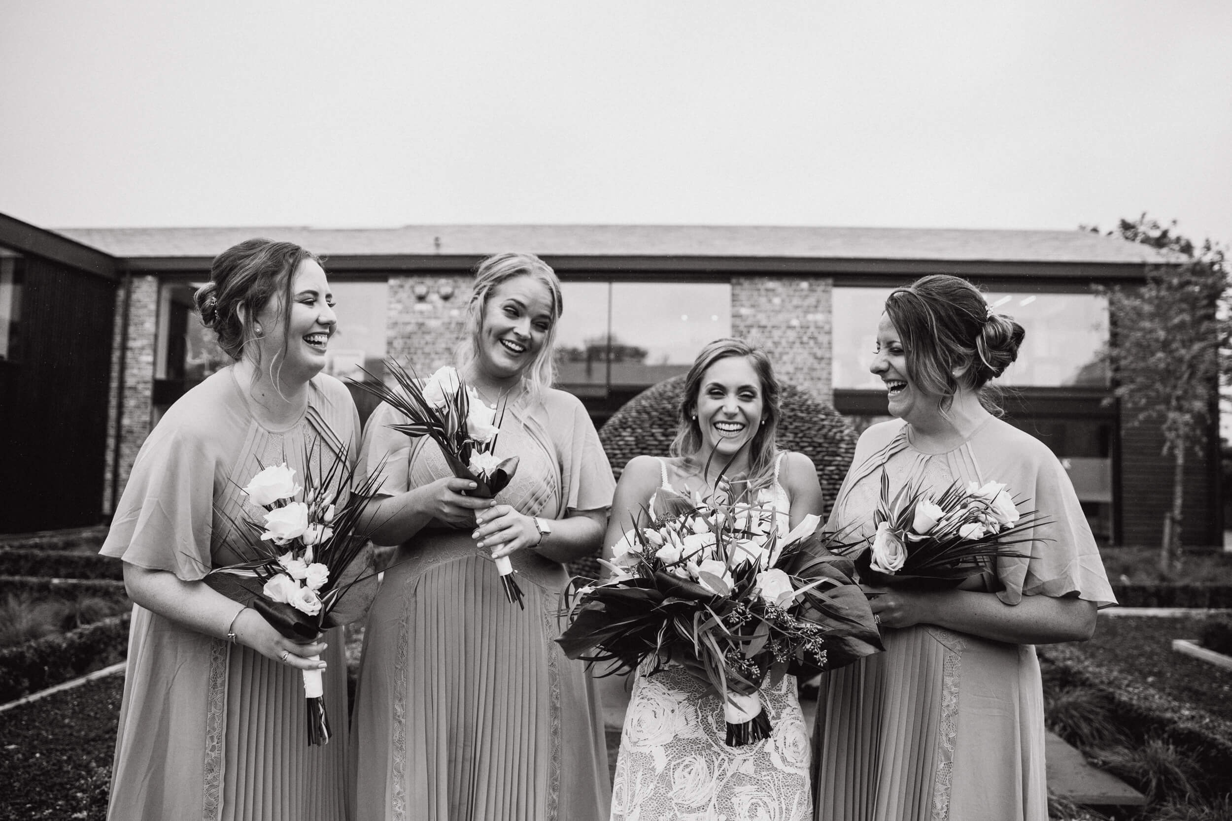 black and white photograph of bride laughing with bridesmaids at colony base