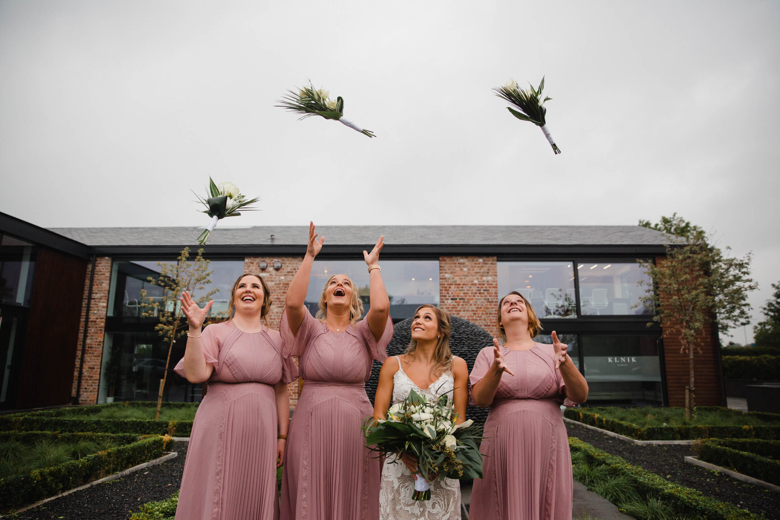 bridesmaids throw wedding bouquets in air