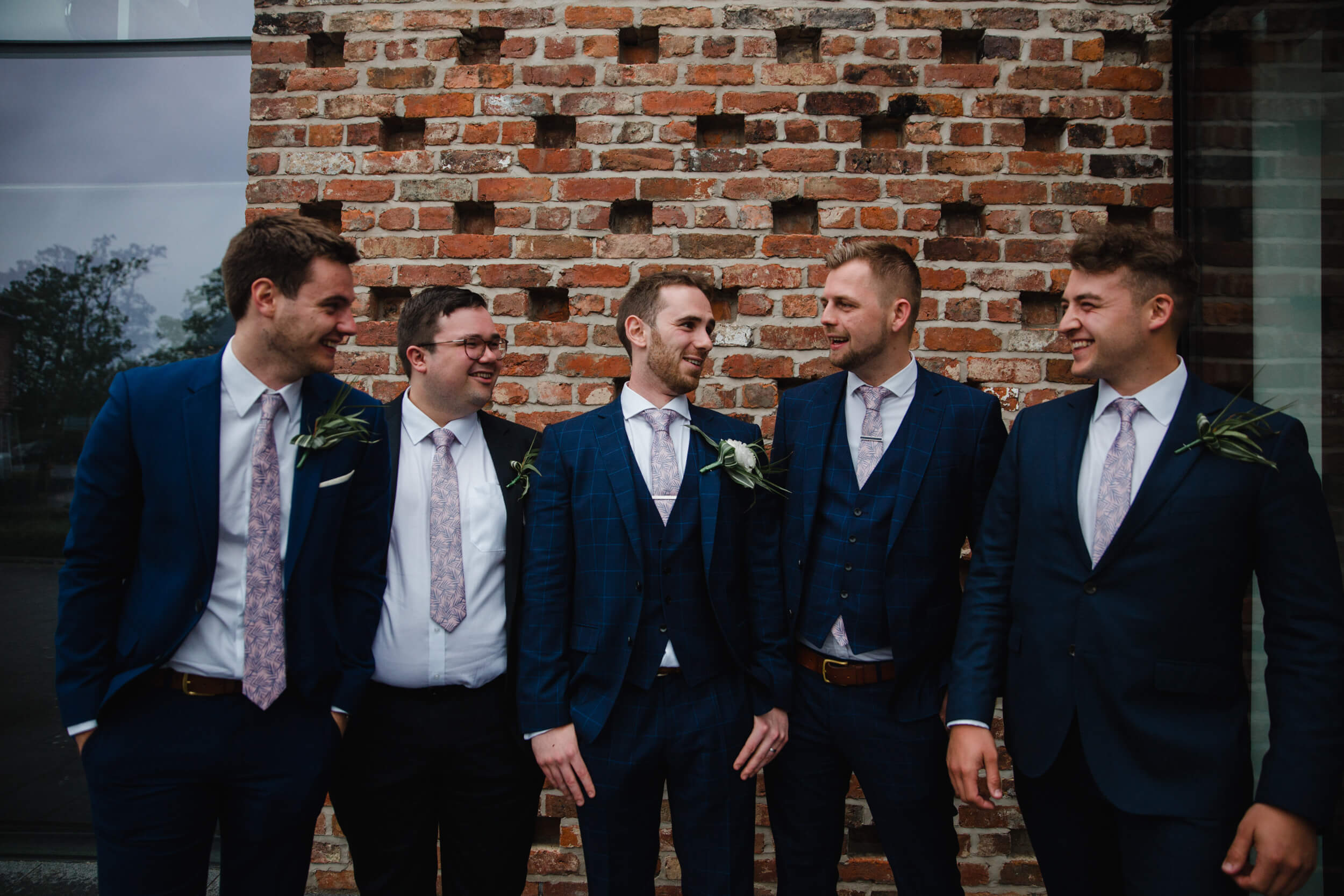 groomsmen in suits pose for group photograph in front of guardhouse