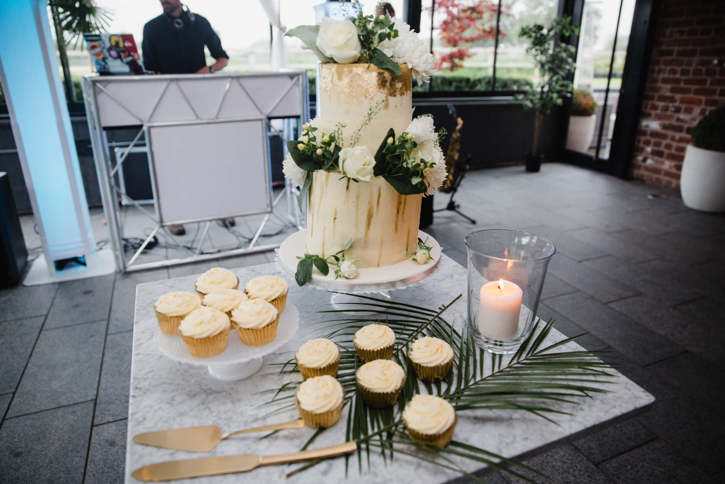 wedding cake and cupcakes dressed with bouquet flowers