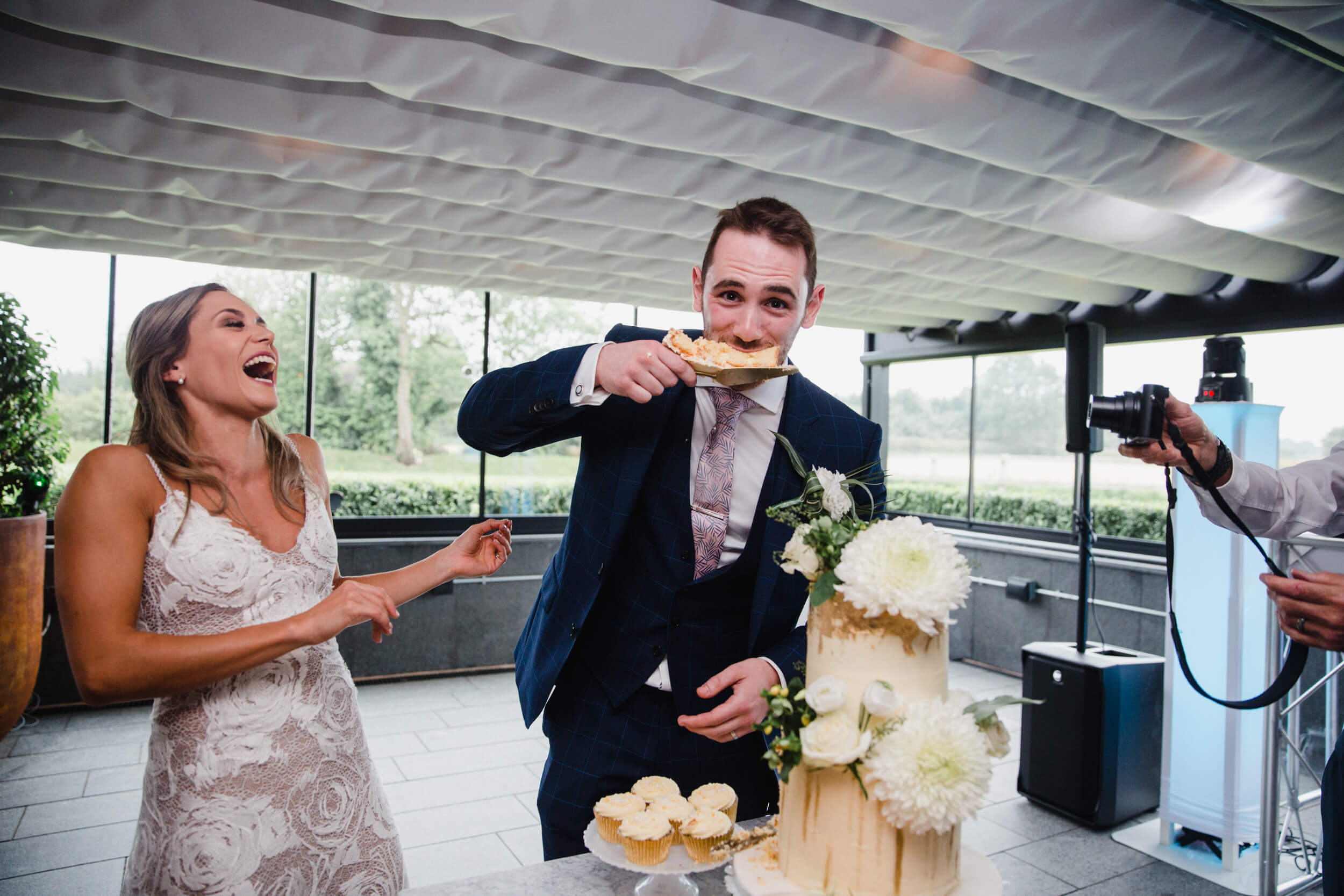 groom eats slice of wedding cake with bride laughing at The Colony HQ