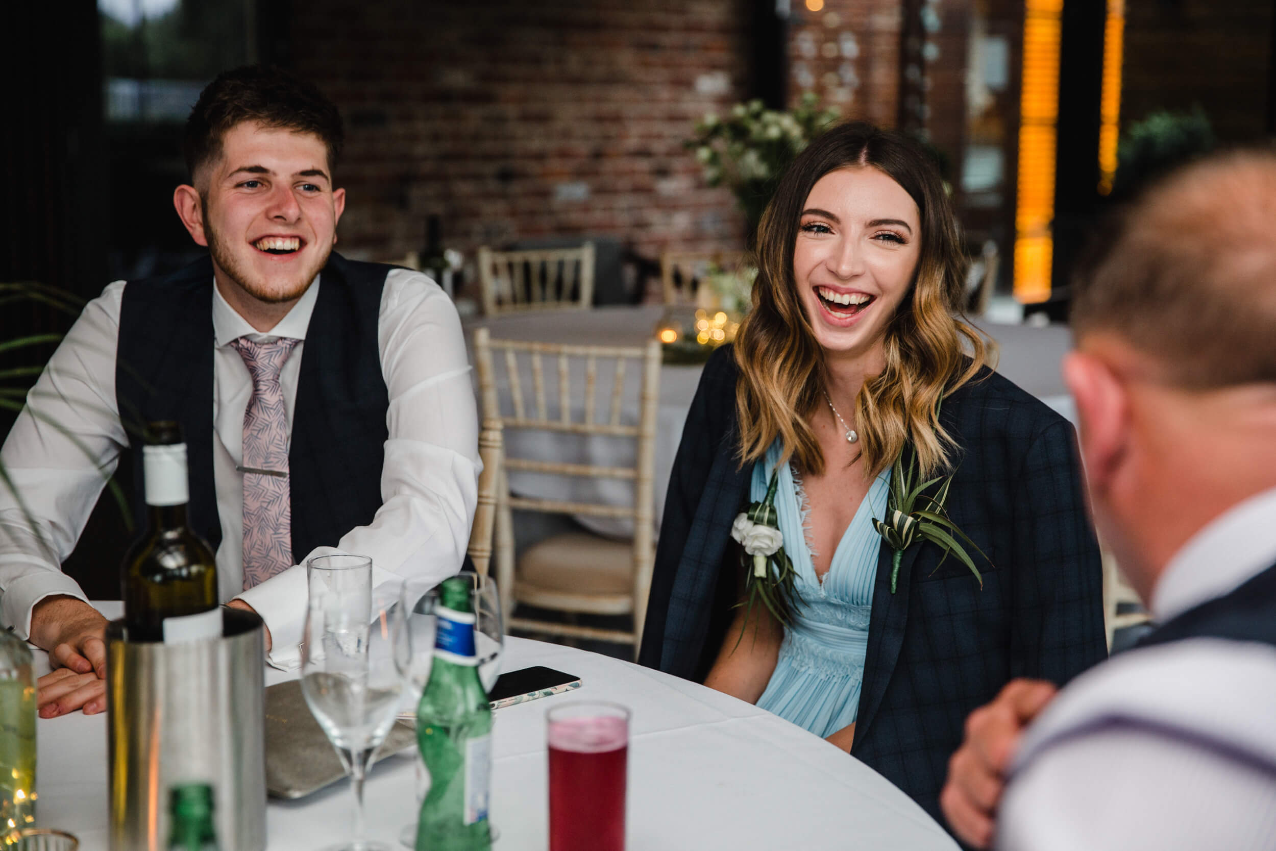 wedding guests laughing at base jokes with family