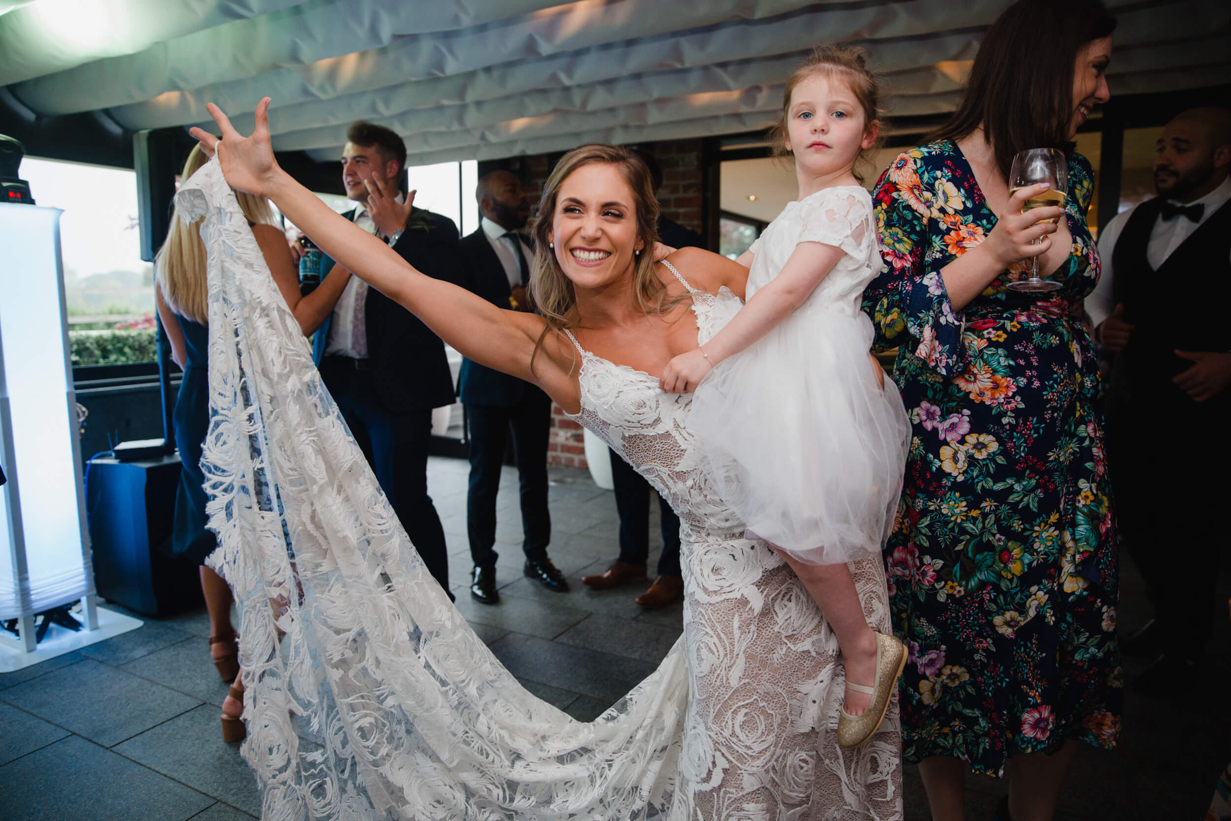 bride holding flower girl lifting wedding dress up off the dance floor