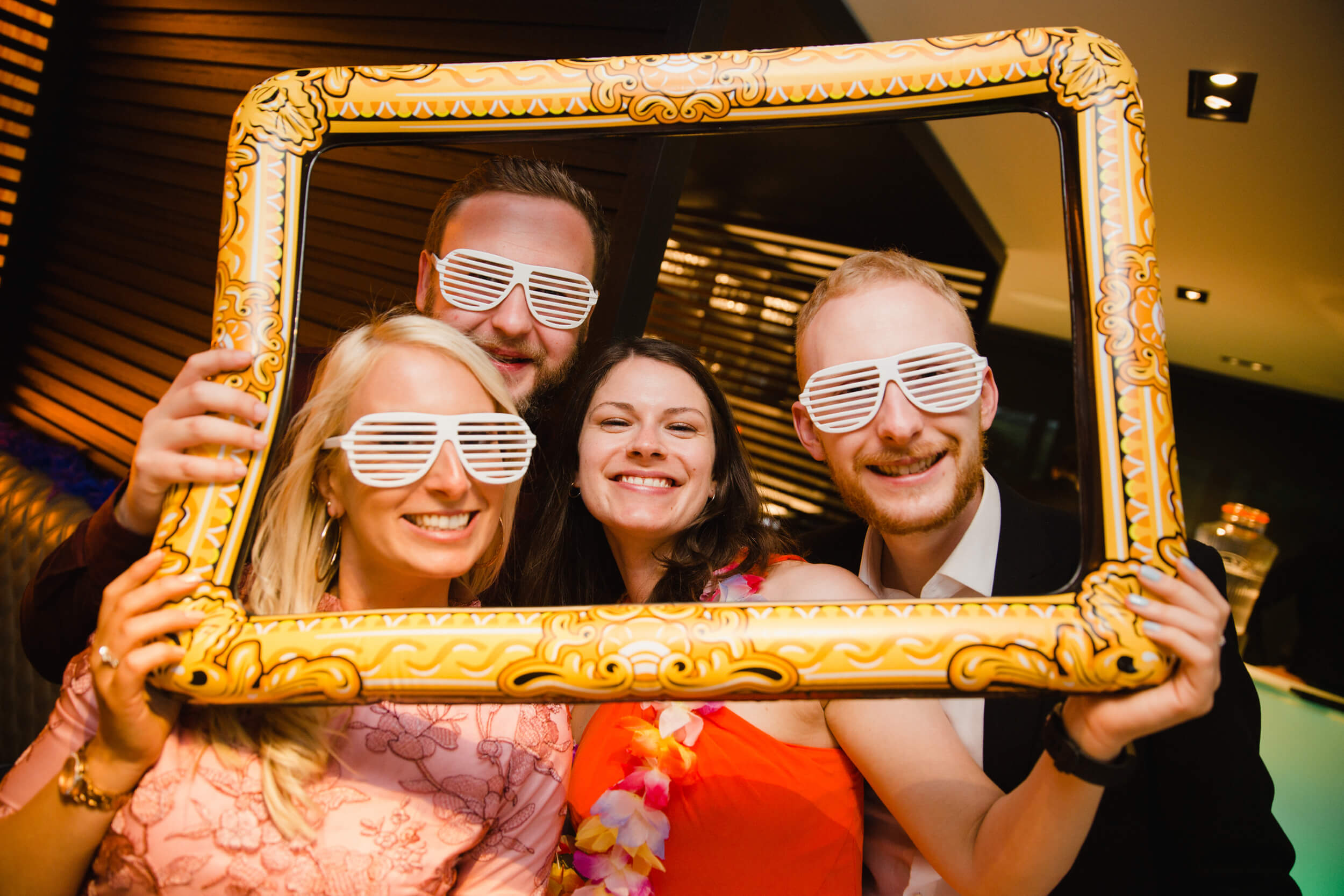 wedding guests settle for pose in frame for photograph