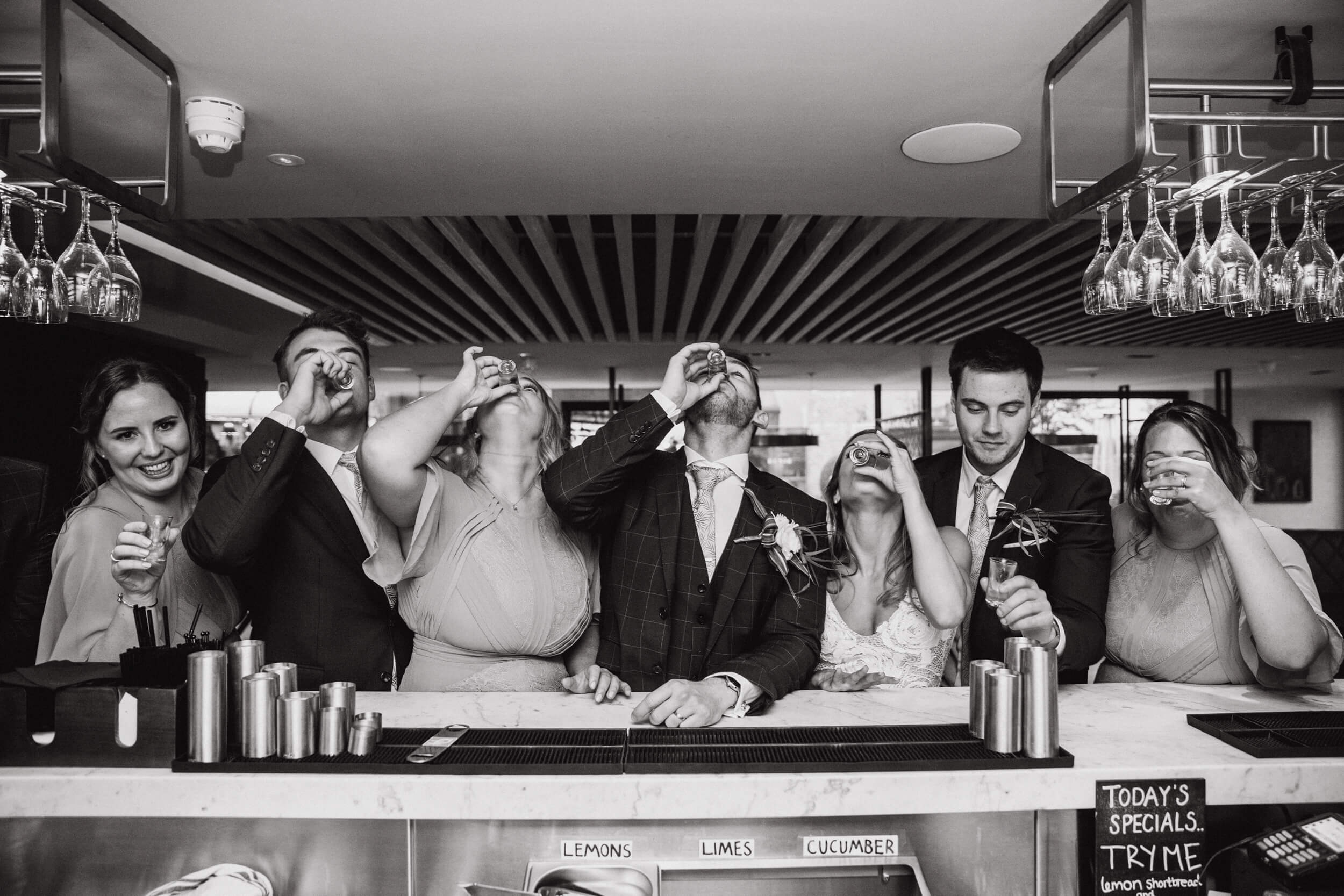 bridal black and white photograph of bridal party drinking at bar of the colony HQ