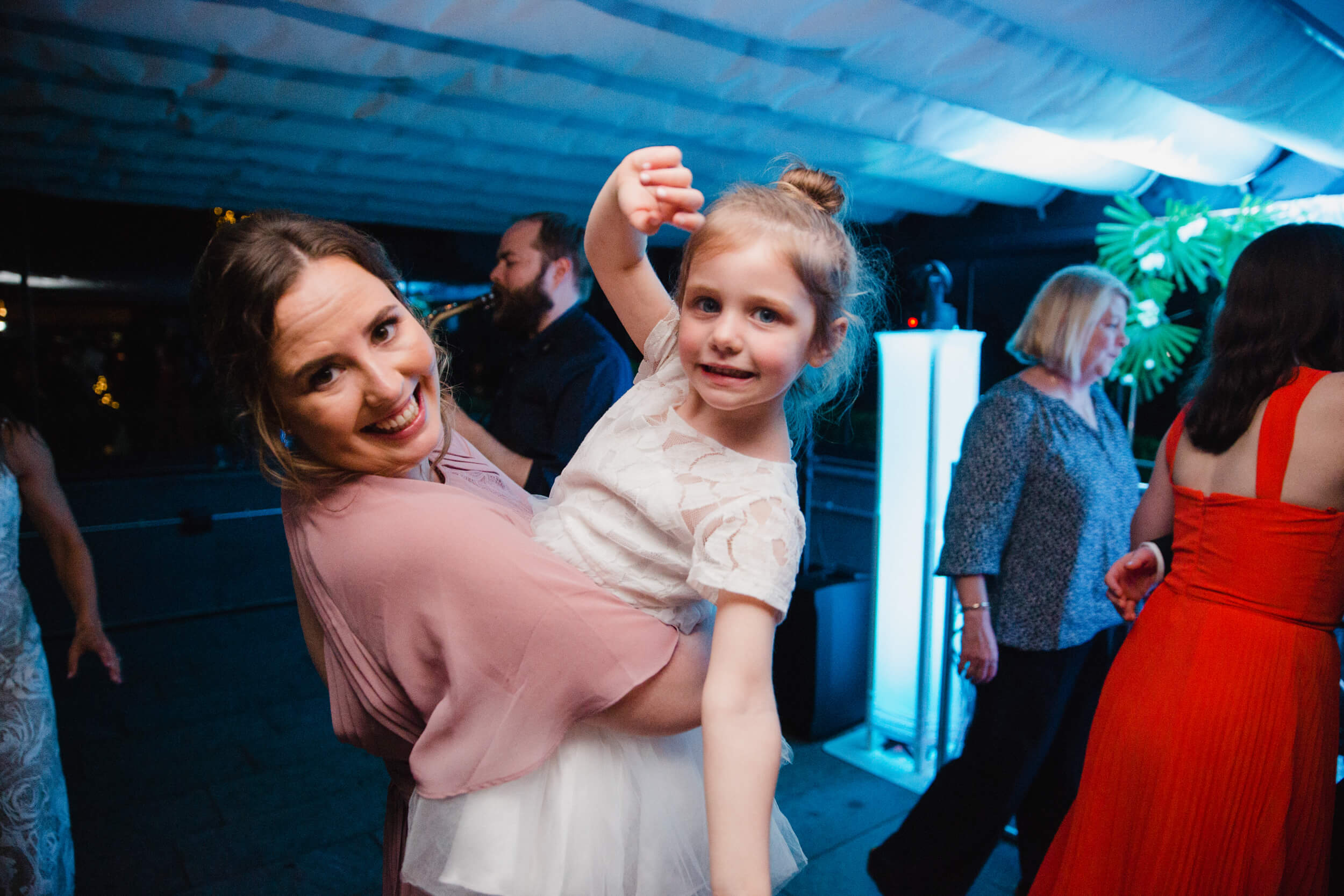 bridesmaid holding flower girl on dance floor of wedding