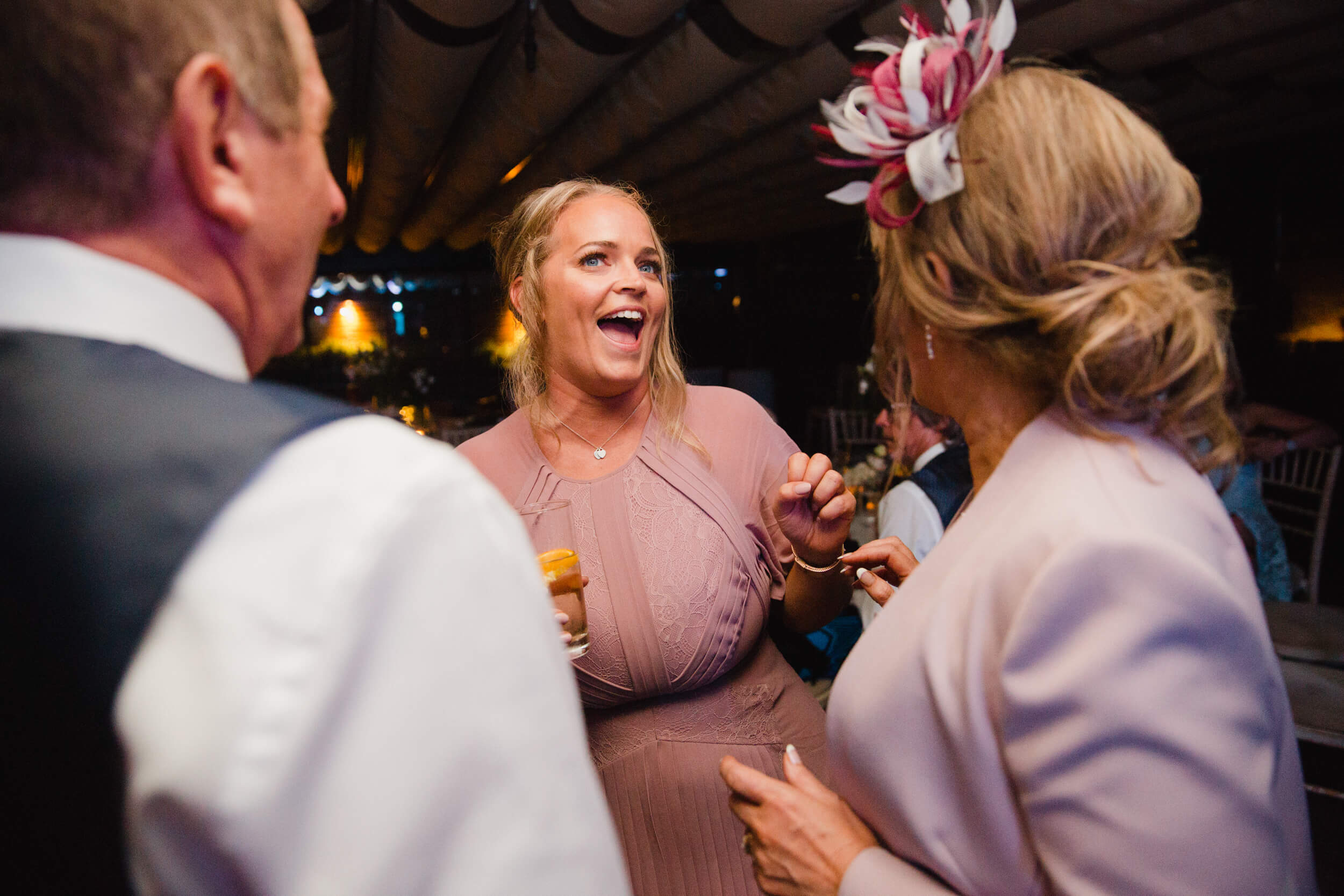 maid of honour sharing joke with bridal party after ceremony
