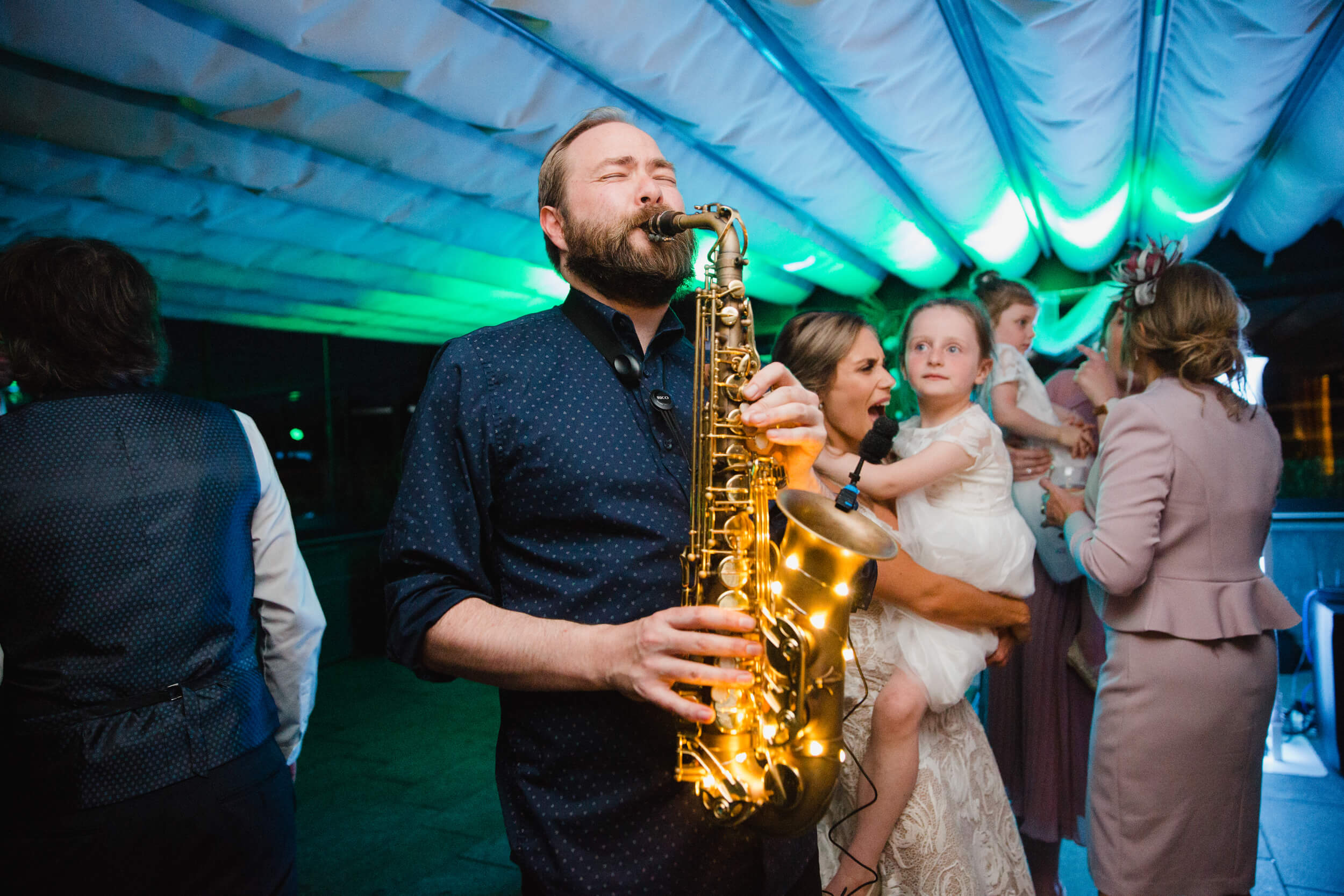 saxophone player plays to wedding party at the colony hq