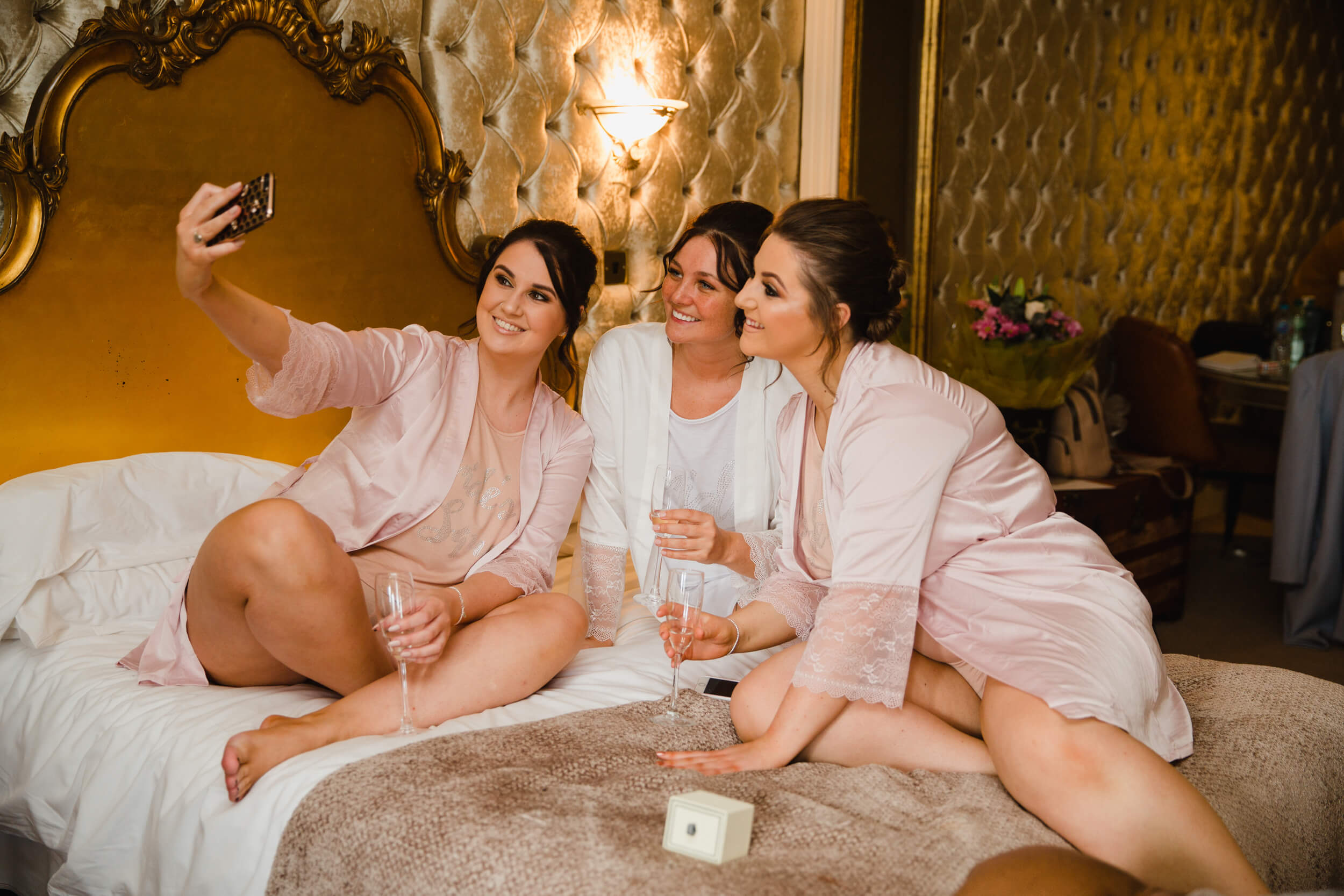 bridesmaids and bride taking phone camera photographs on bed