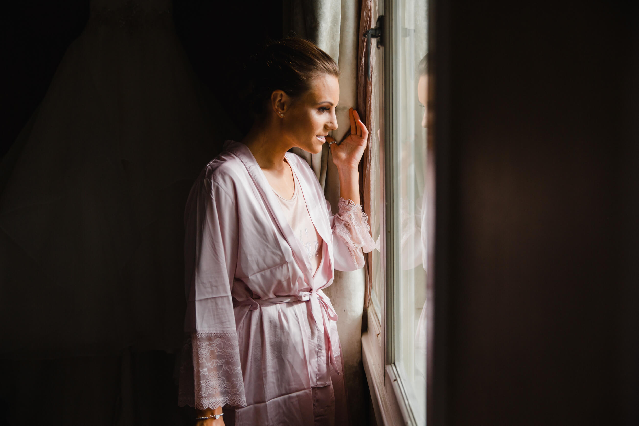 bridesmaid looking out of window down on street corner