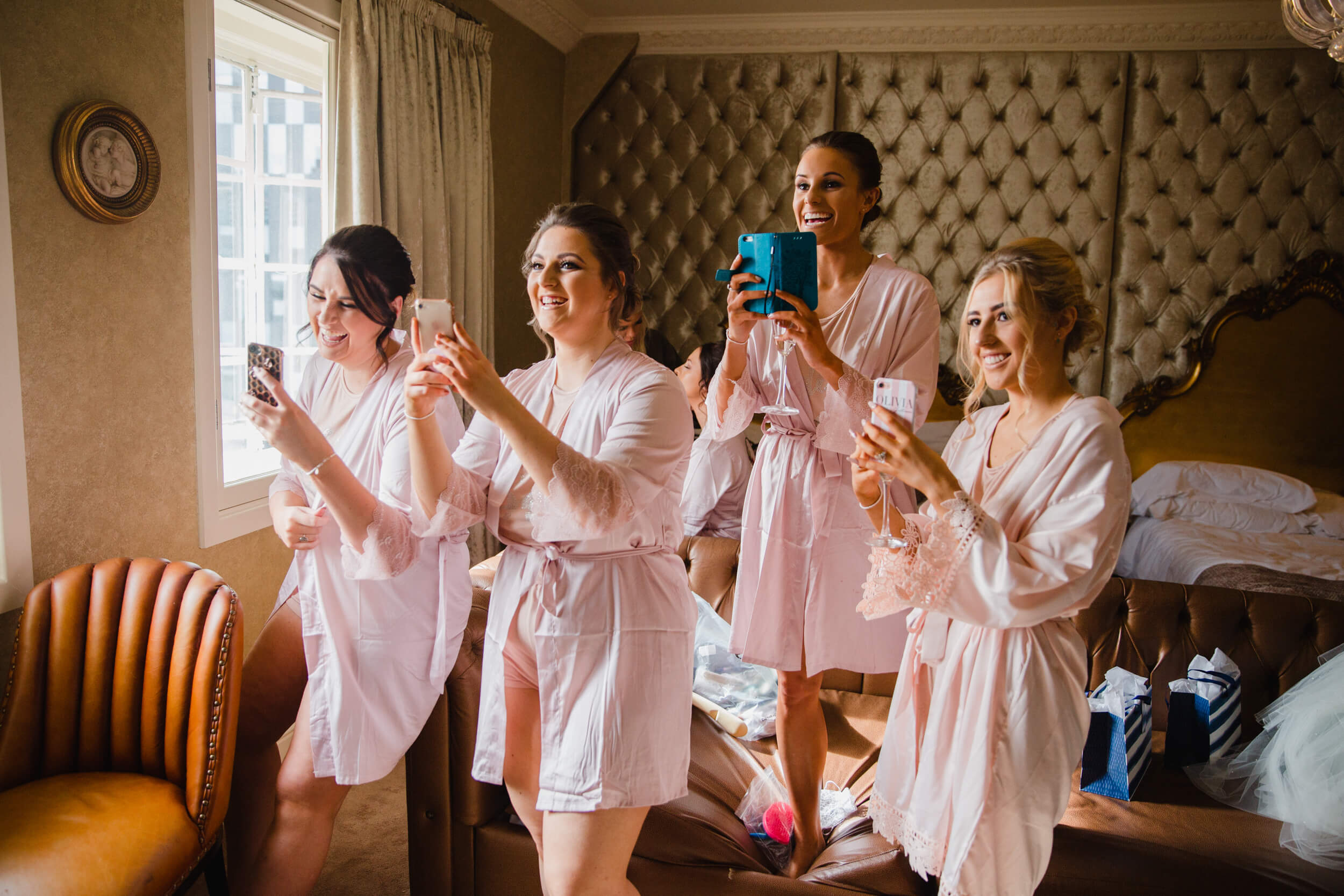all bridesmaids in hotel suite taking photographs of bride