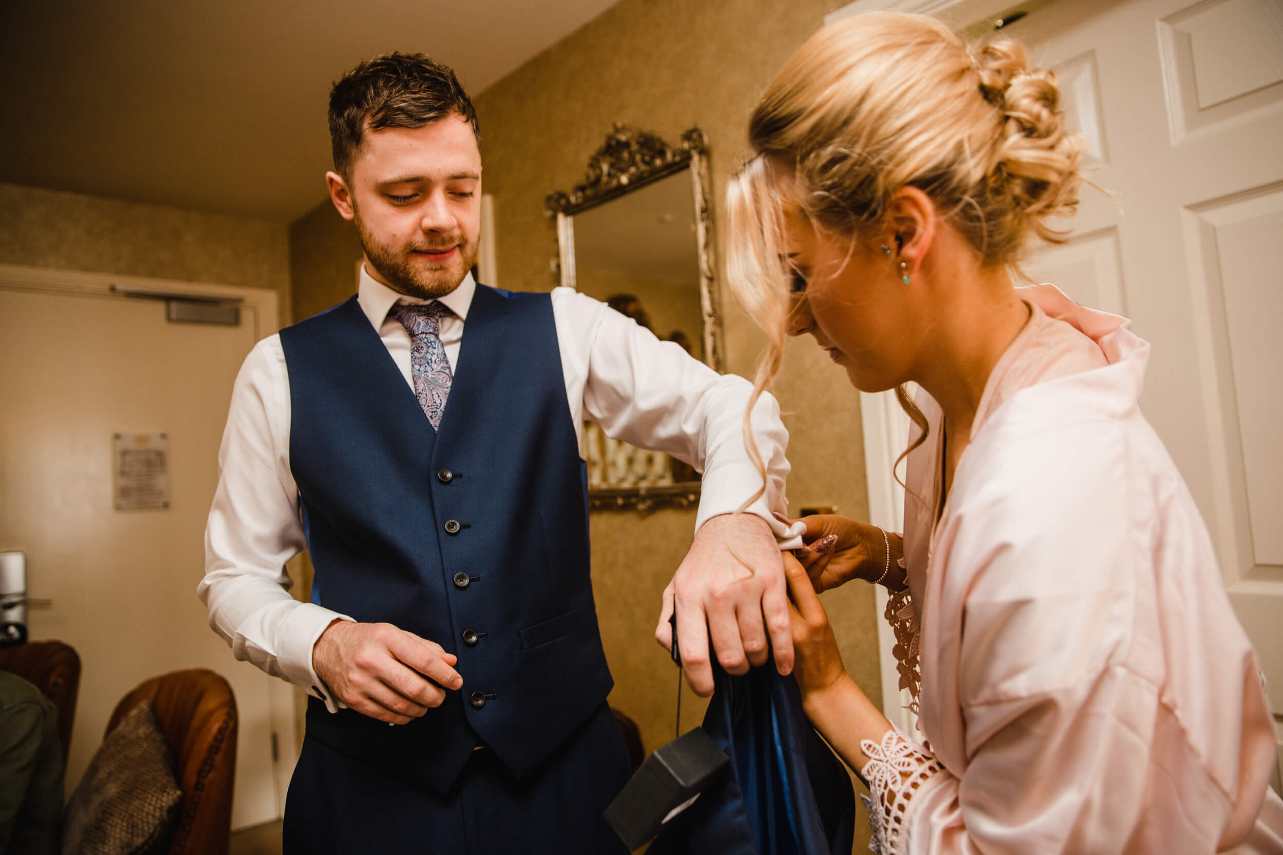 groomsman having suit cufflink attached by maid of honour