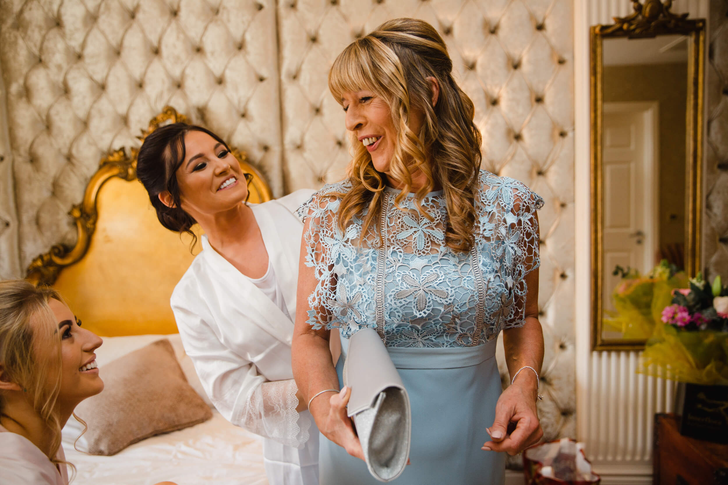 mother of bride sharing relaxed natural moment with bride and bridesmaids