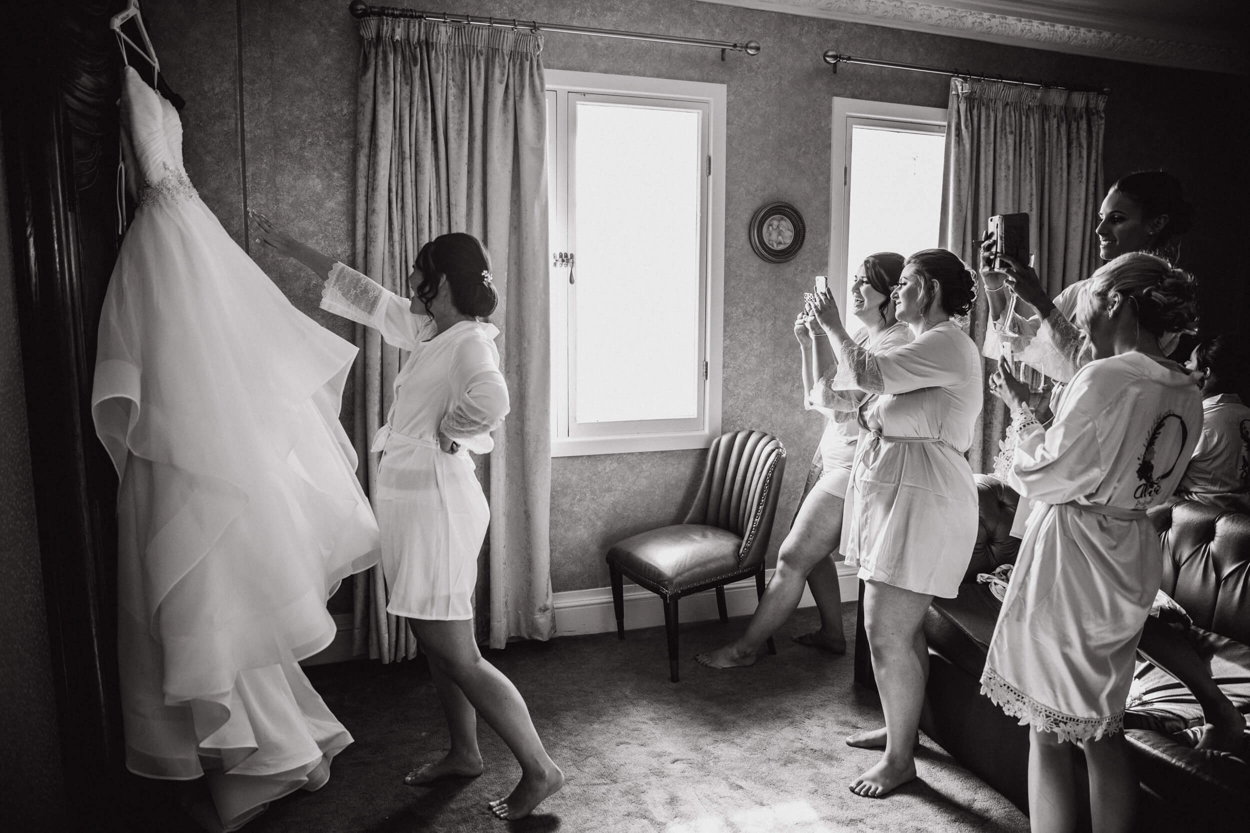 black and white photograph of bride and bridesmaids hanging up wedding dress