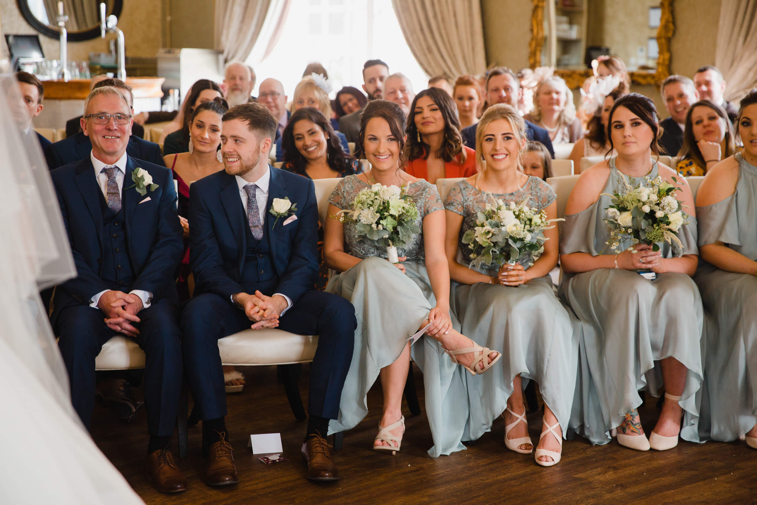 bridesmaids smiling for bride and groom during vows
