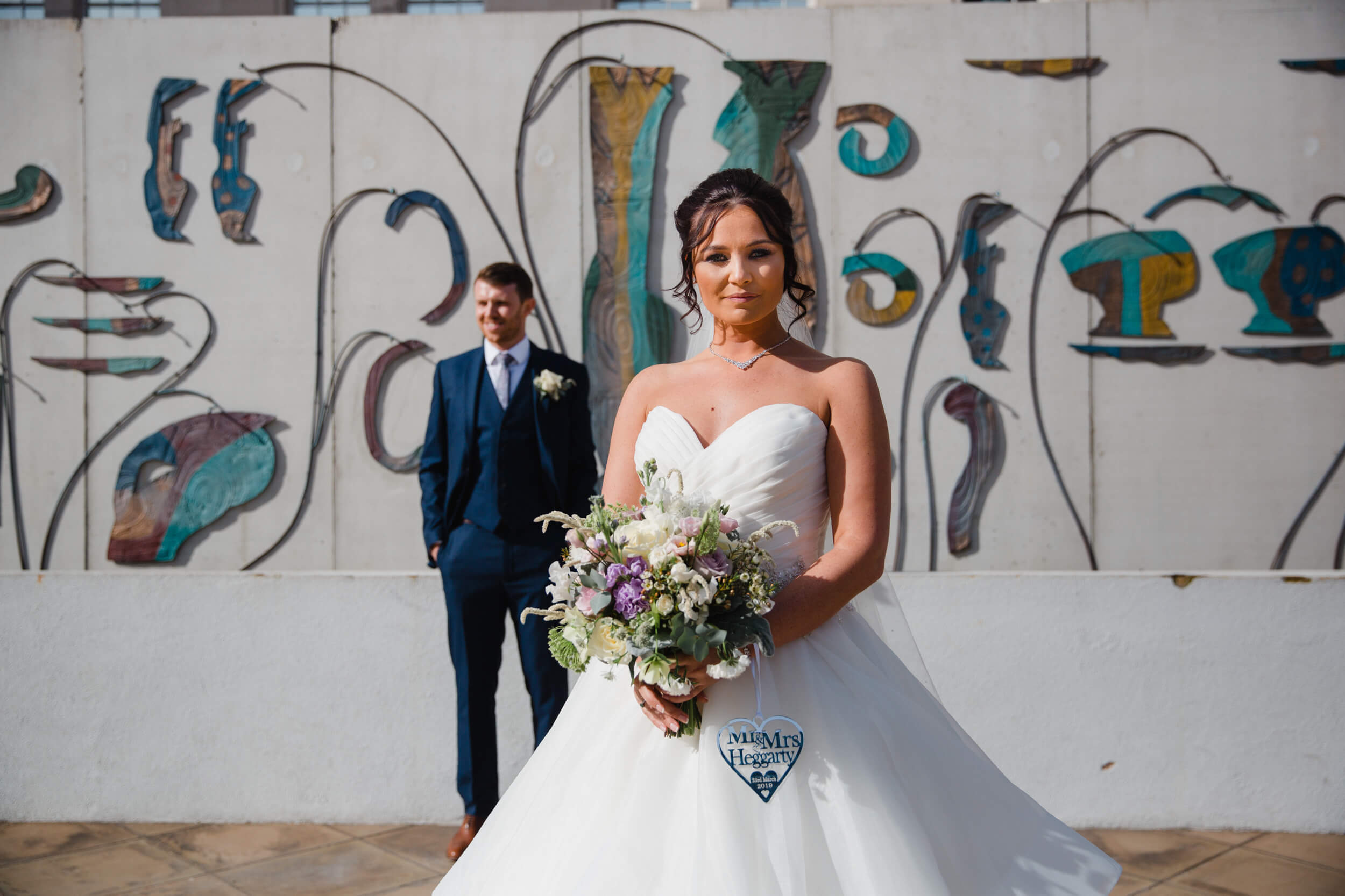 bride in foreground of photograph posing with bouquet