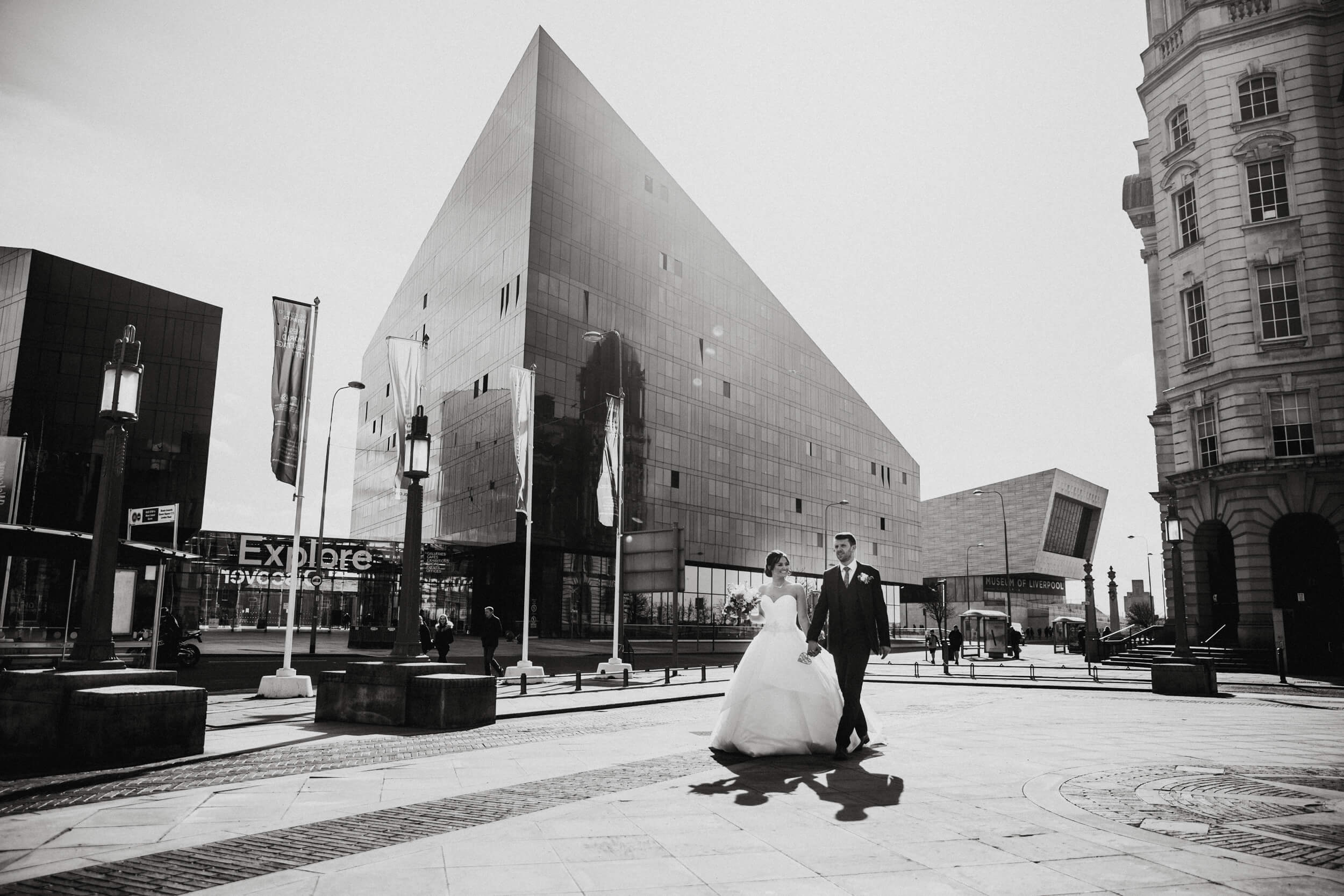black and white photograph of bride and groom walking by Liverpool Docks outside 30 James Street