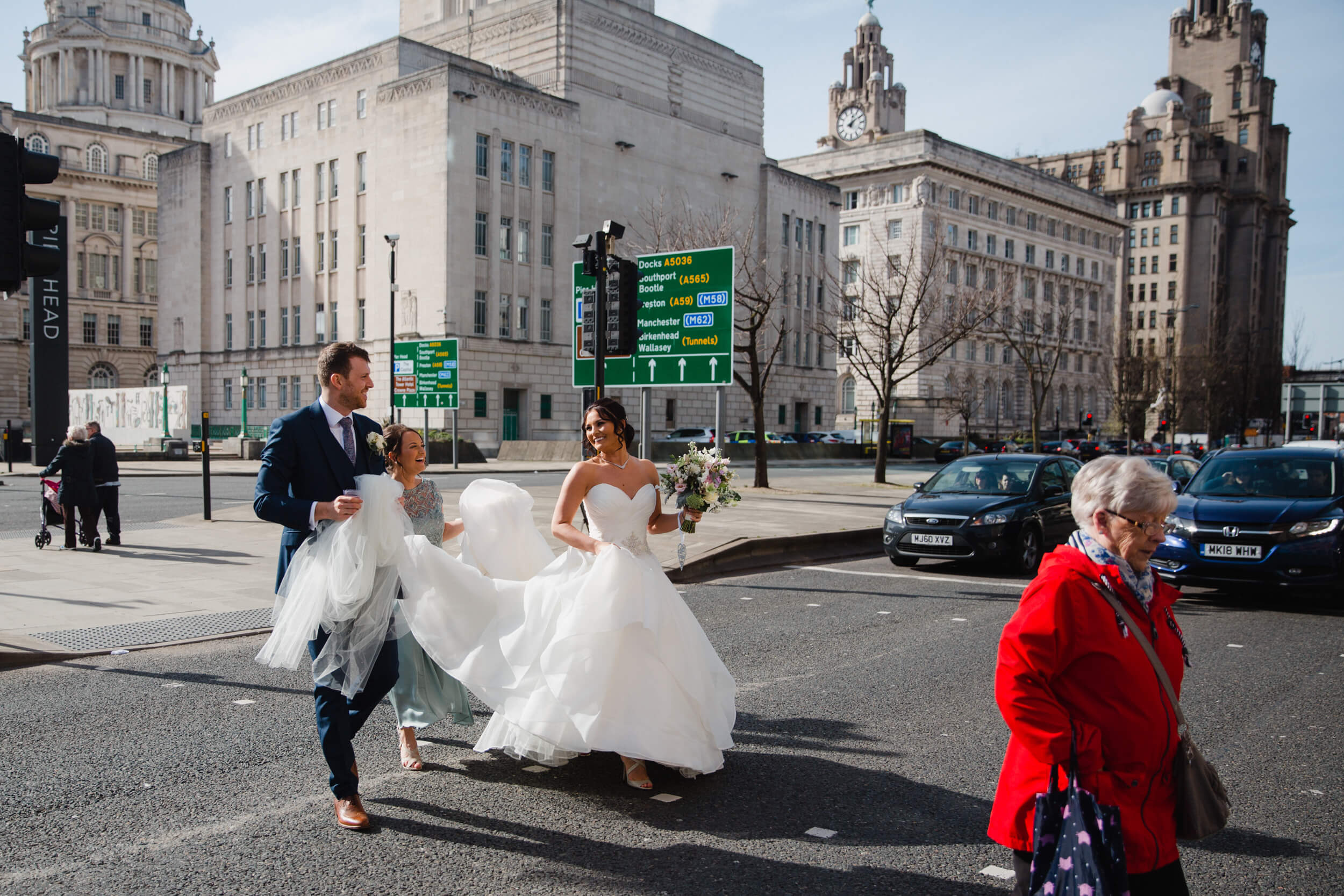 groom and bridesmaid helping carry bride and dress across road at 30 James Street