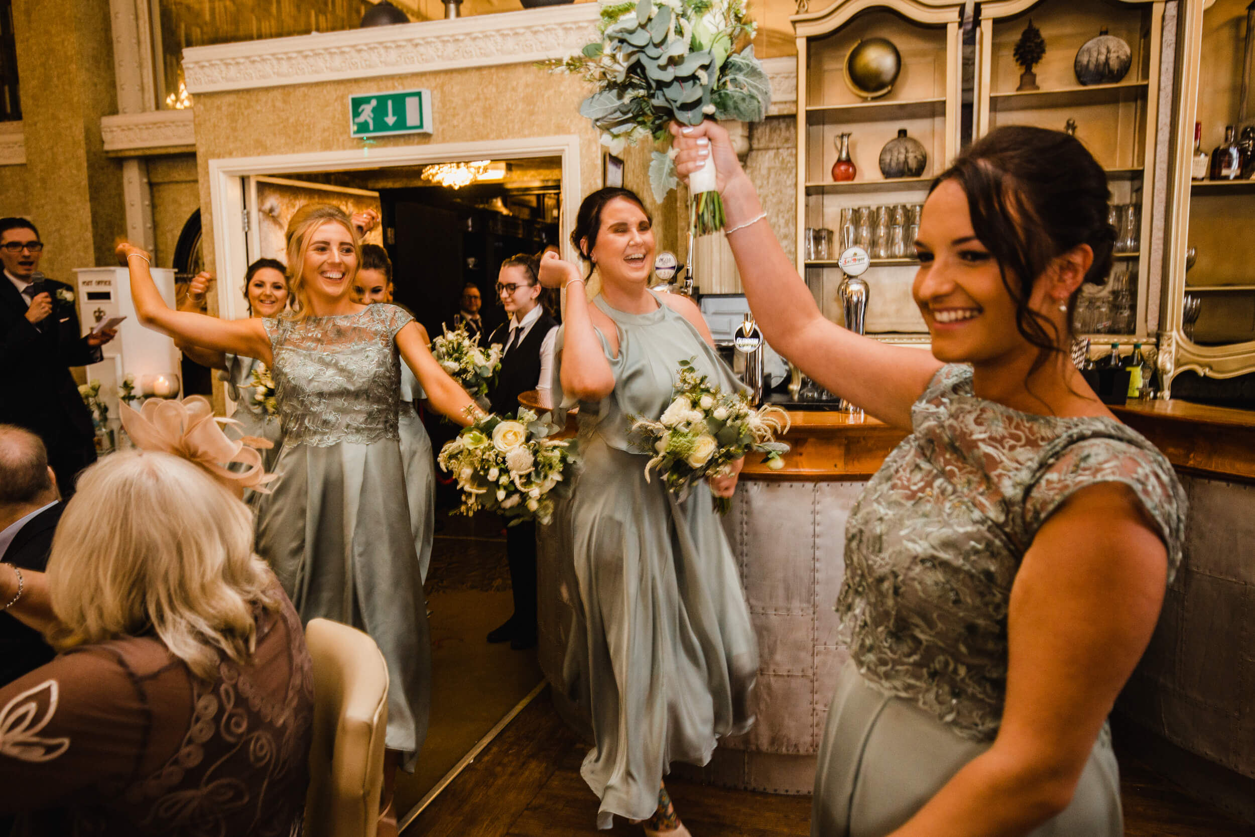 bridesmaids entering wedding breakfast room with dance and waving bouquets in air