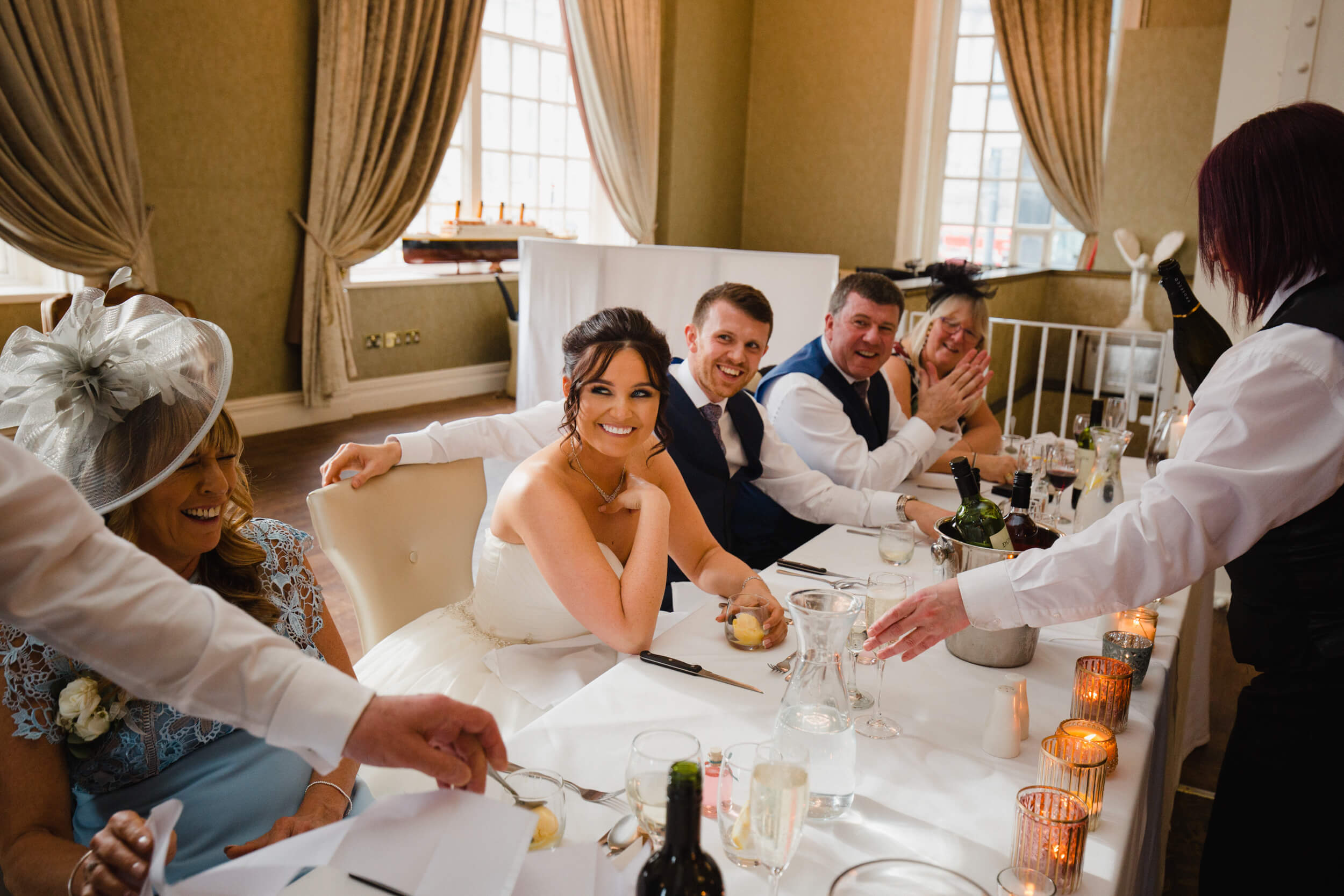bride laughing at fathers speech on top table during wedding breakfast