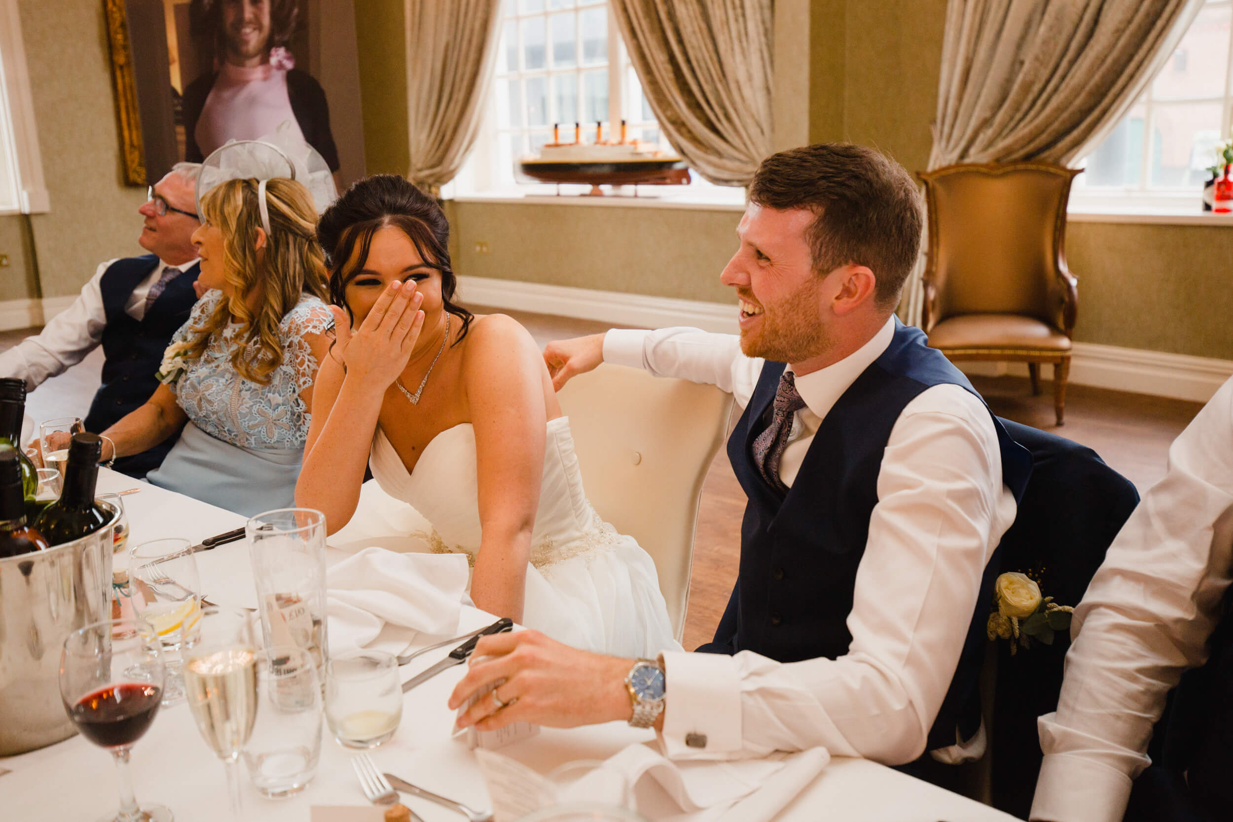 bride with head in hands hides from humorous speech