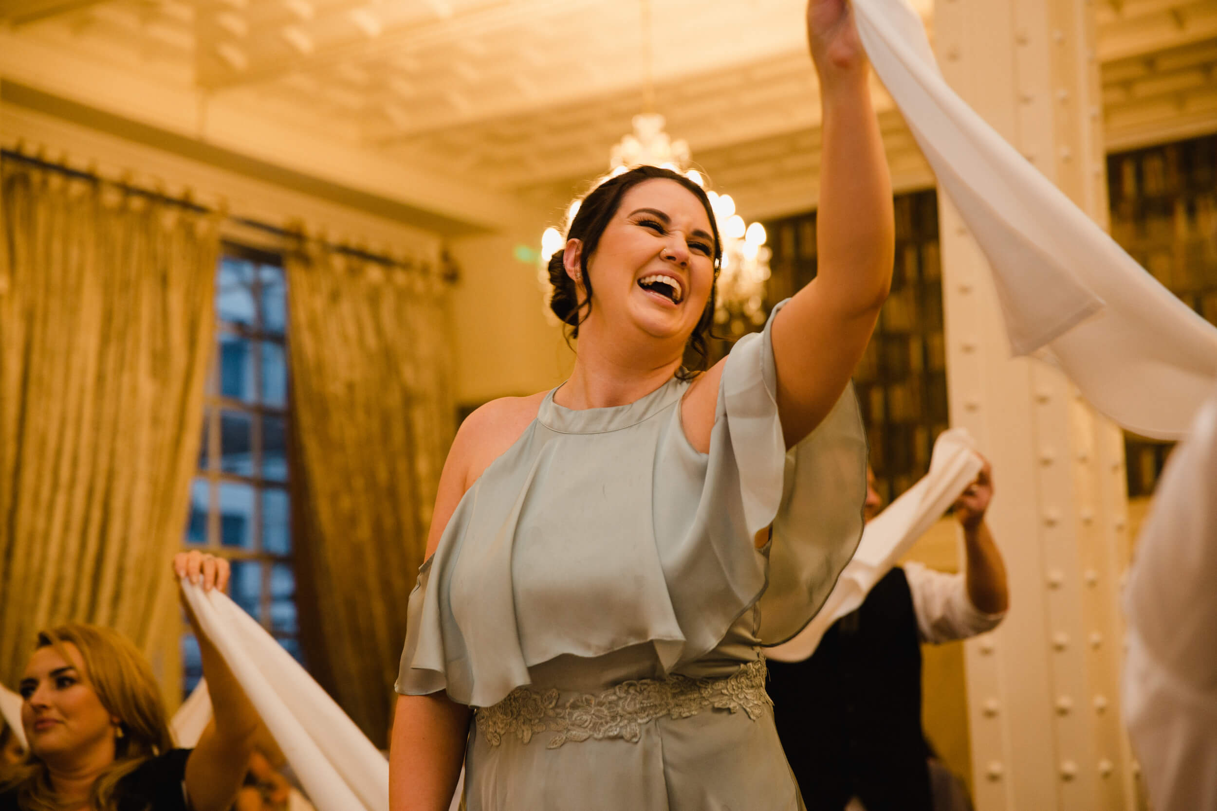 maid of honour waving napkin in the air while laughing
