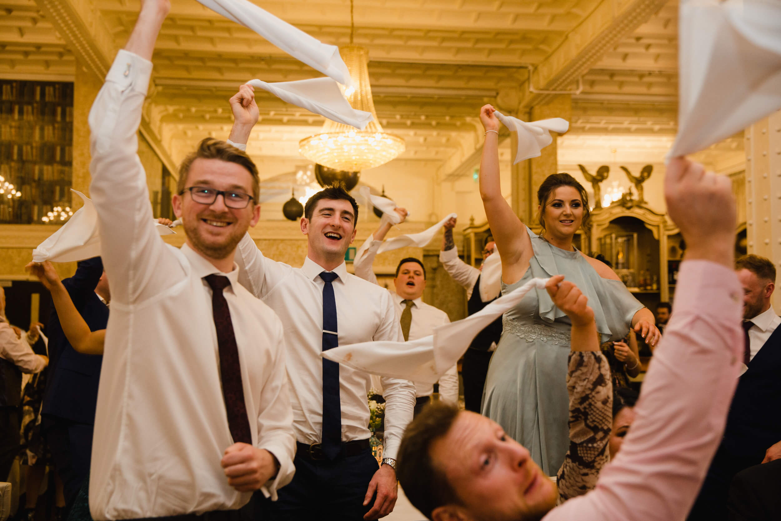 wedding guests waving napkins in the air in celebration